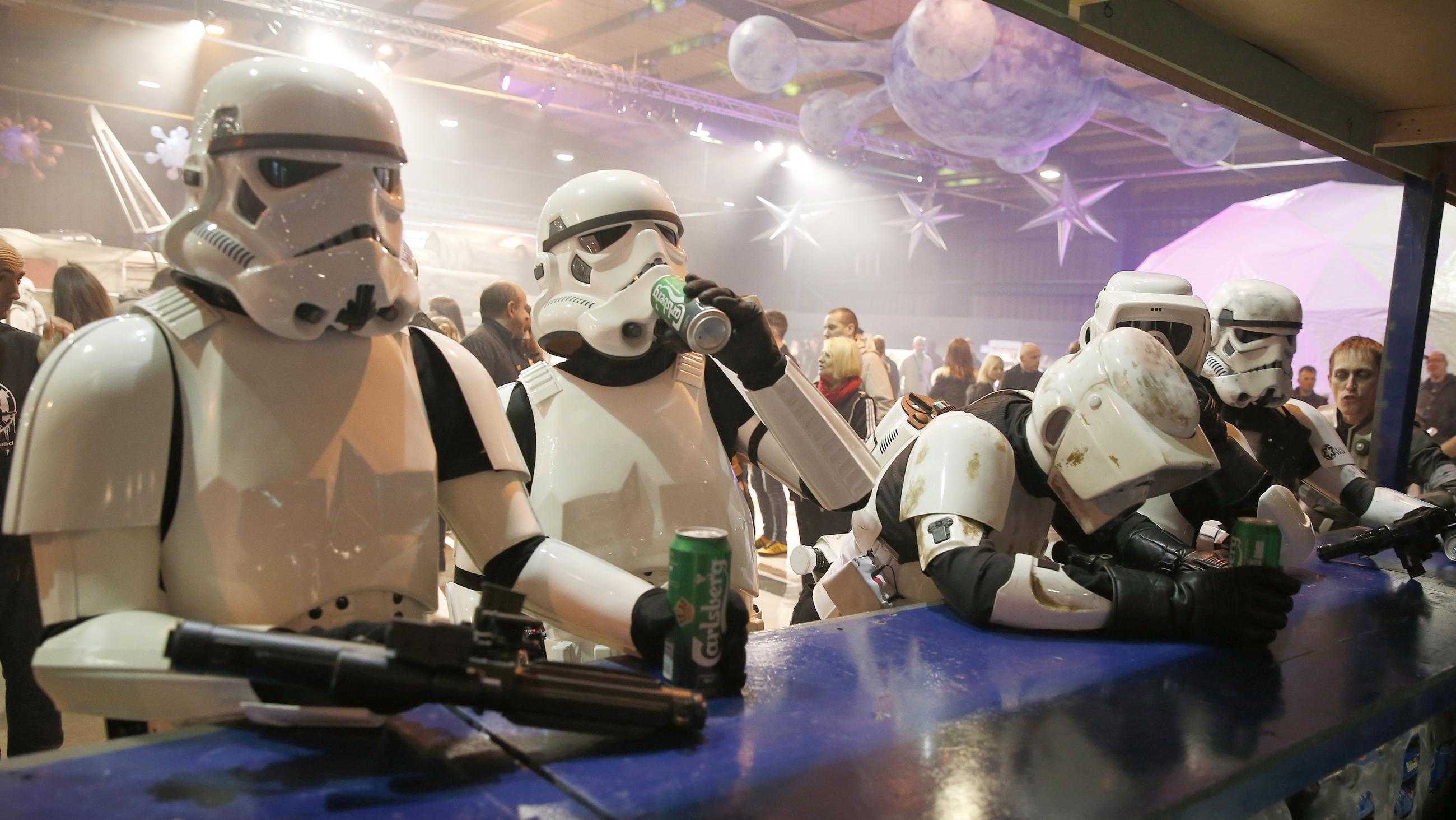 People dressed as Storm troopers stand at a bar as they pose for a photograph holding cans of beer at the 'For The Love of The Force' Star Wars fan convention in Manchester, northern England, December 4, 2015.