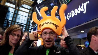 GoDaddy CEO Blake Irving puts on a foam hat on the floor of the New York Stock Exchange as he waits for his company's IPO to begin trading, Wednesday, April 1, 2015. (AP Photo/Richard Drew)
