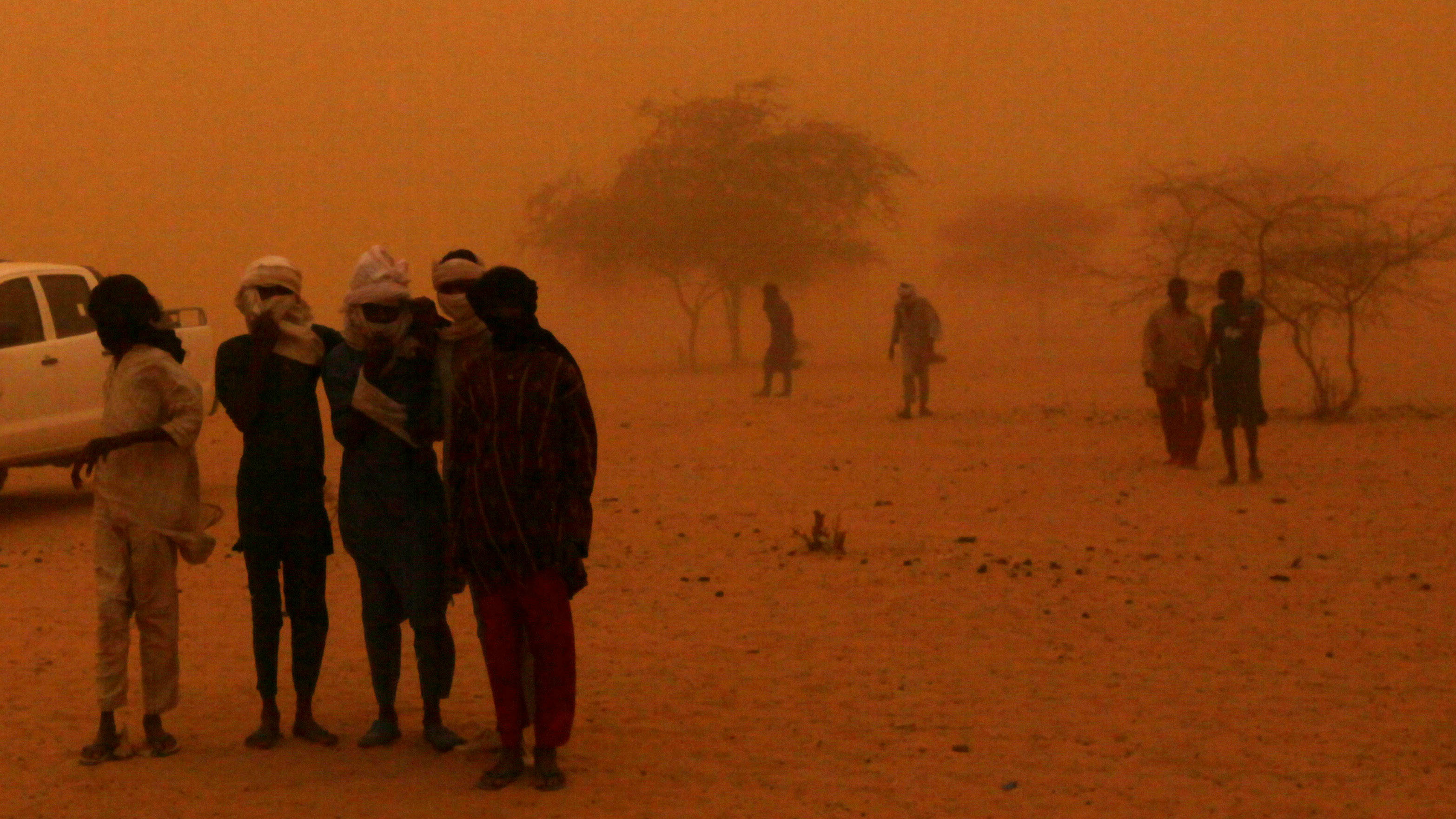 In this Tuesday, May 11, 2010 photo, a sandstorm engulfs Fulani herdsmen near their temporary settlement in Gadabeji, Niger. At this time of year, the Gadabeji Reserve should be a refuge for the nomadic tribes who travel across the moonscape deserts of Niger to graze their cattle. But the grass is meager, not enough even for the small goats, after a drought killed off the last year's crops. International aid groups once again warn this nation of 15 million on the verge of the Sahara Desert faces a growing food crisis.