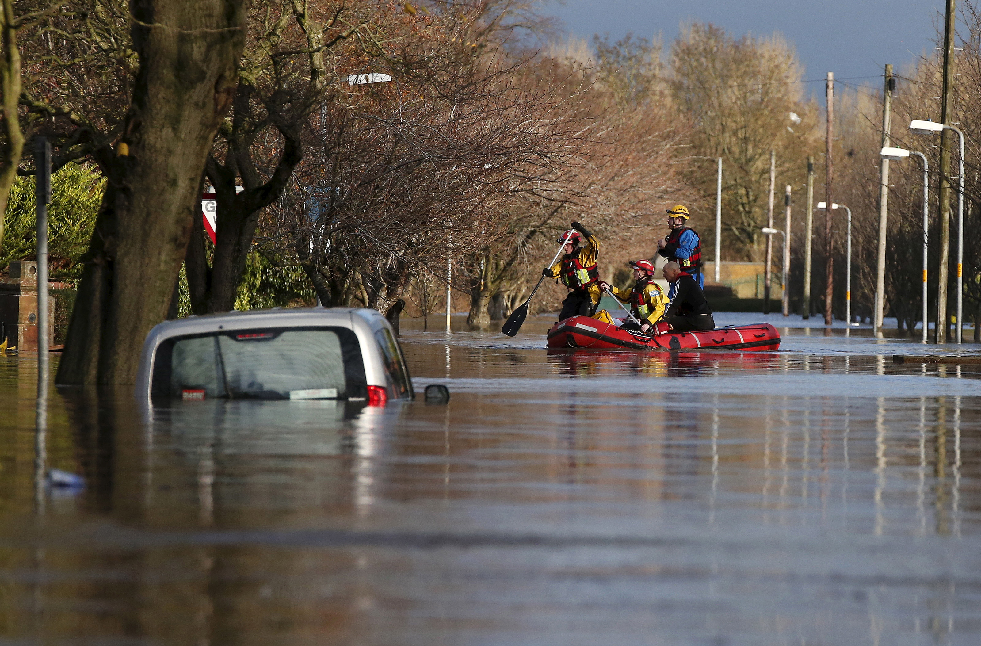 Rescue workers remove local residents by boat from a flooded residential street in Carlisle, Britain December 6, 2015. British police have declared a major incident in northern England after prolonged heavy rain caused widespread flooding and forced emergency services to evacuate residents from their homes. REUTERS/Phil Noble