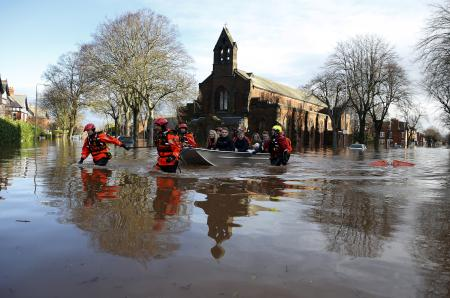 Rescue workers pull a boat full of rescued residents along a flooded residential street in Carlisle, Britain December 6, 2015. REUTERS/Phil Noble