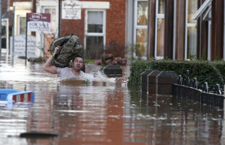 A local resident carries a bag as he wades through flood water on a residential street in Carlisle, Britain December 6, 2015. British police have declared a major incident in northern England after prolonged heavy rain caused widespread flooding and forced emergency services to evacuate residents from their homes. REUTERS/Phil Noble