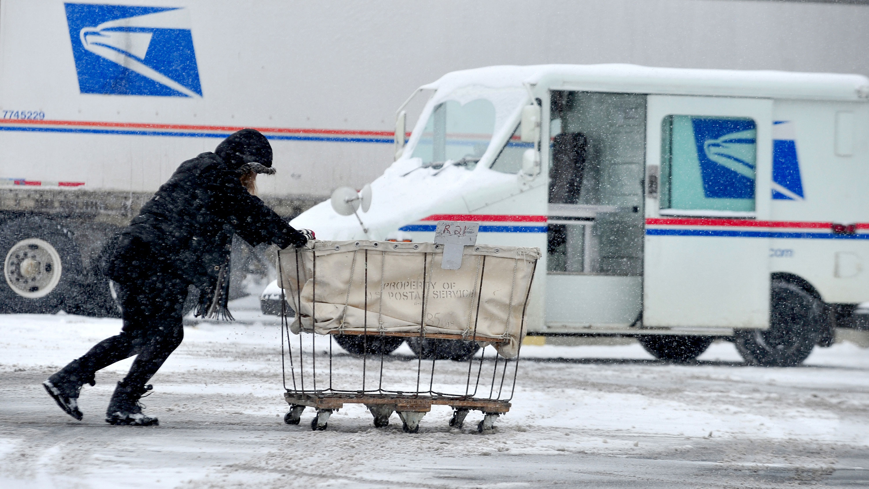USPS carrier Stephanie Starr, of Seymour, pushes a mail cart from her carrier vehicle to the loading dock area of the Columbus, Ind. Post Office, Tuesday, Feb. 9, 2010. Starr has been working as a carrier for eight years and said that although she is used to delivering in inclimate weather she said her rural route near Taylorsville takes about two hours longer to complete when there is heavy snow. (AP Photo/The Republic, Joel Philippsen)