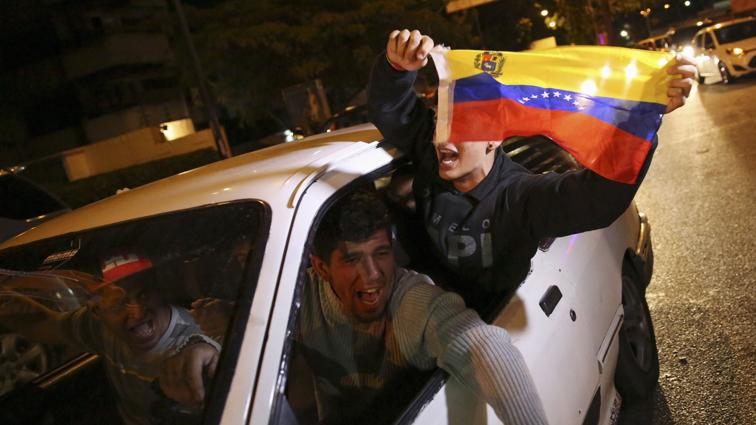 Supporters of the opposition Democratic Unity coalition wave a Venezuelan national flag from a car while they celebrate their victory on a street in Caracas.