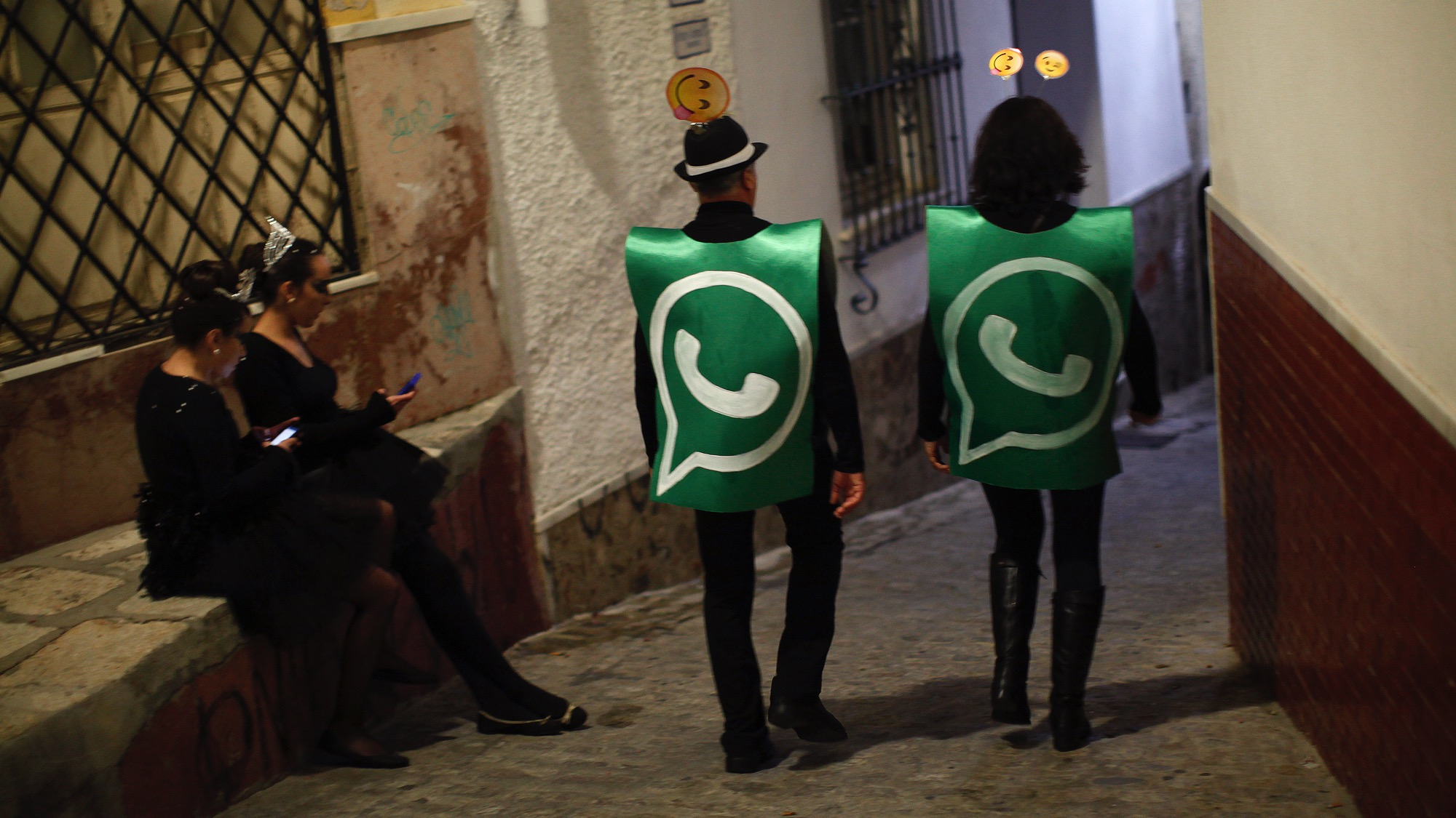 Revellers dressed up as dancers of 'Black Swan' check their mobile phones next to revellers dressed up as a Whatsapp logo as they take part in New Year's celebrations in Coin, near Malaga, southern Spain, early January 1, 2015. Villagers and revellers dressed up in funny costumes to take part in the New Year's celebration. REUTERS/Jon Nazca (SPAIN - Tags: SOCIETY ANNIVERSARY TPX IMAGES OF THE DAY) - RTR4JT1Z
