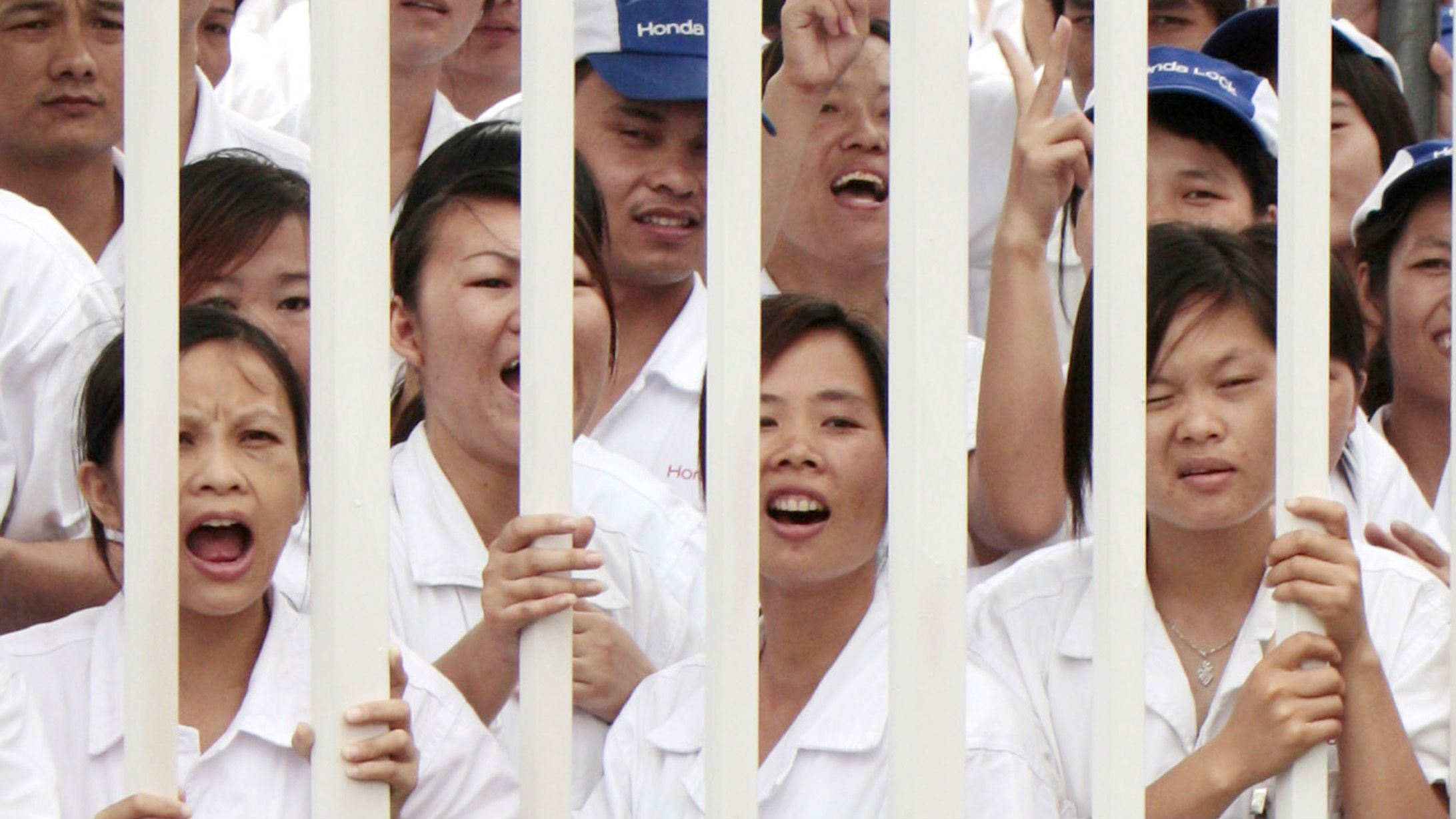 Workers react as they stand by a fence during a strike at a Honda Motor vehicle manufacturing plant in Zhongshan, Guangdong province June 10,2010. Honda Motor said it would resume building cars in China on Friday after a supplier of exhaust systems contained a labour dispute, but workers at another parts maker remained on strike. REUTERS/Tyrone Siu (CHINA - Tags: TRANSPORT BUSINESS)