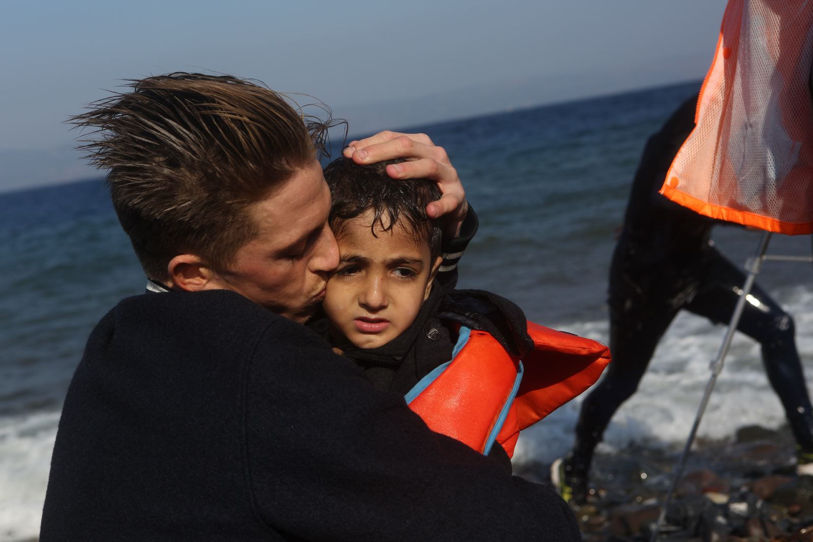 A father and son embrace after arriving in Lesbos, Greece.
