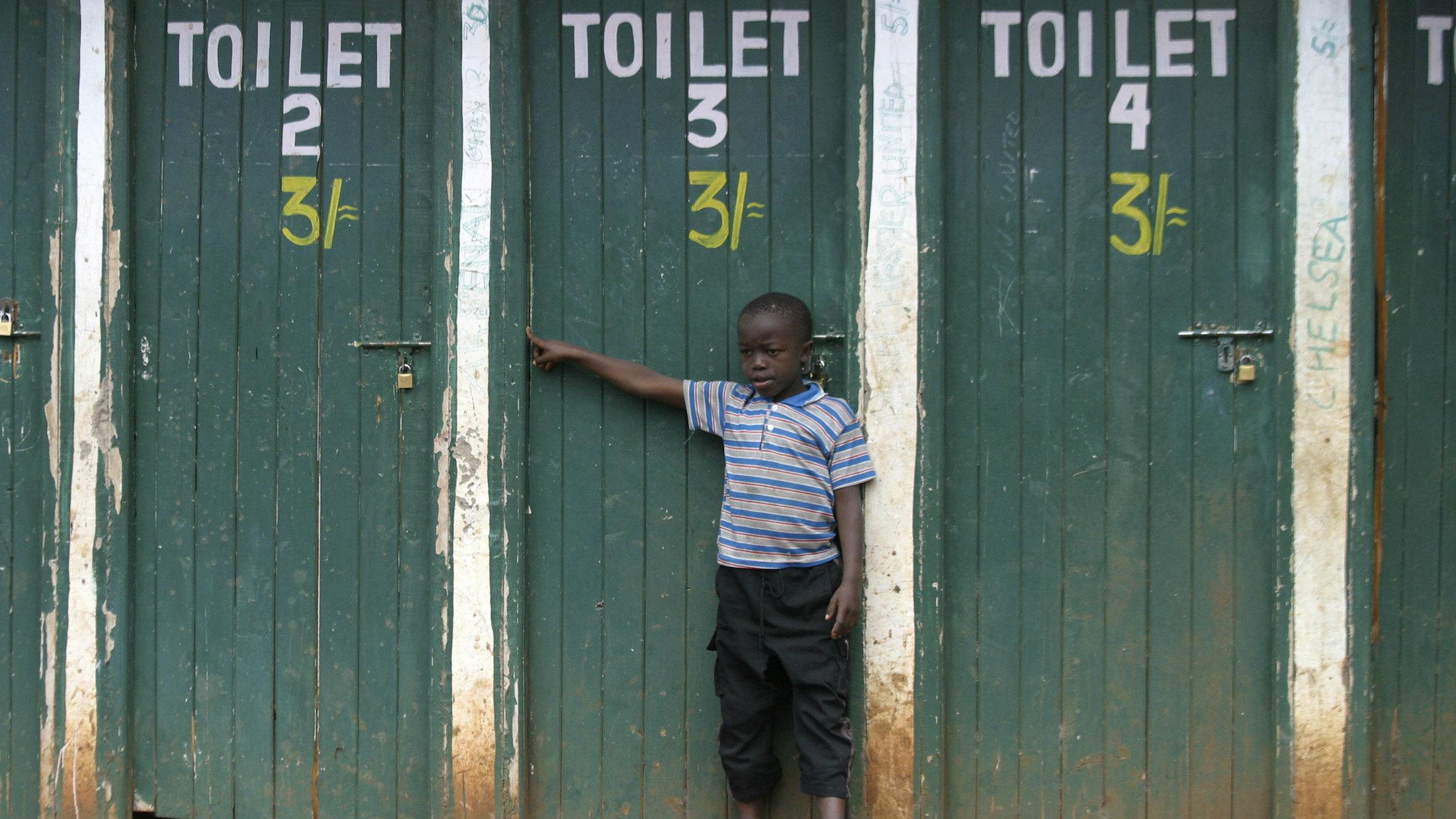A boy stands next to public bathrooms in Nairobi's slum, Kibera