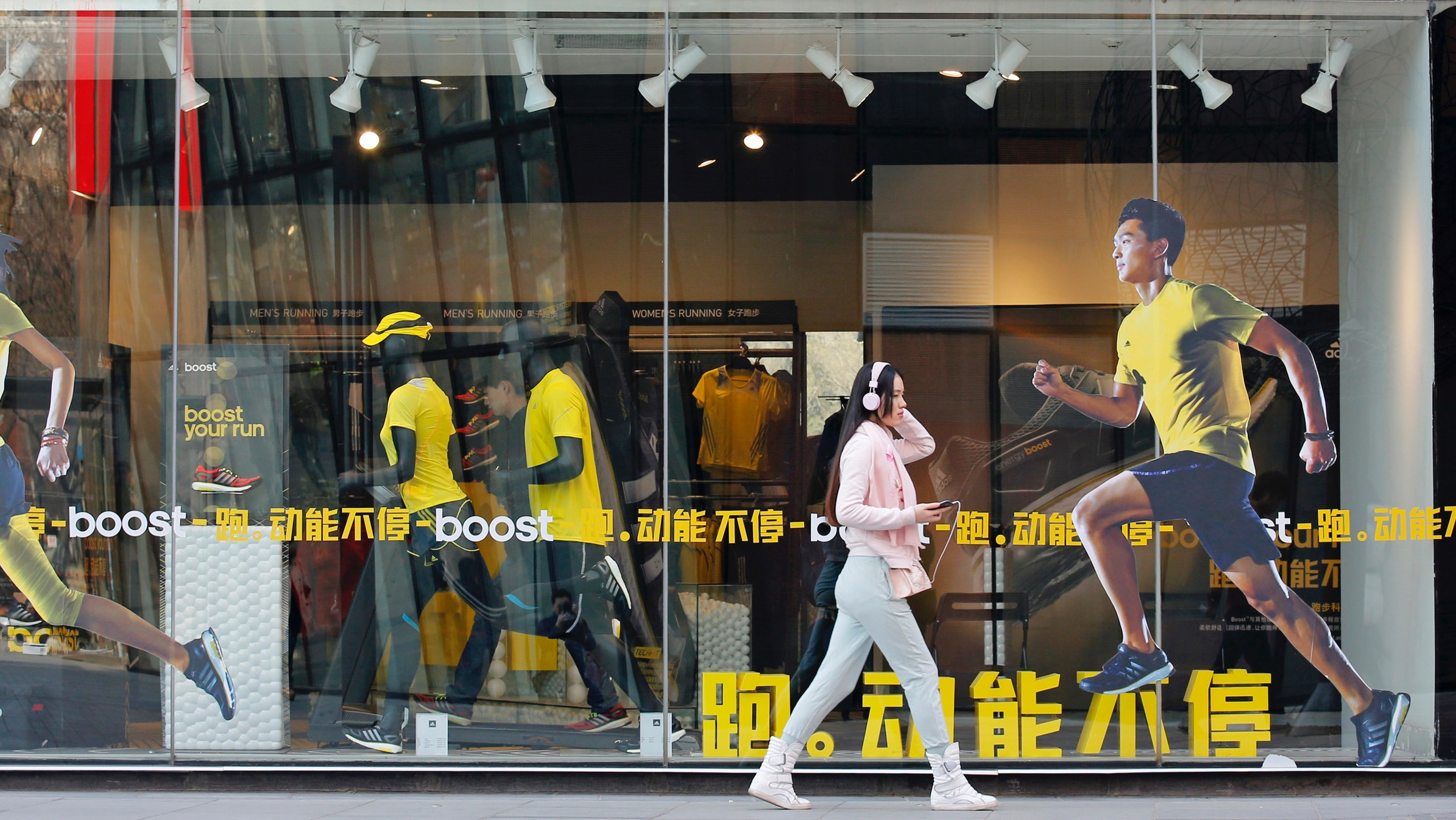 A woman walks past an Adidas shop at a shopping district in Beijing