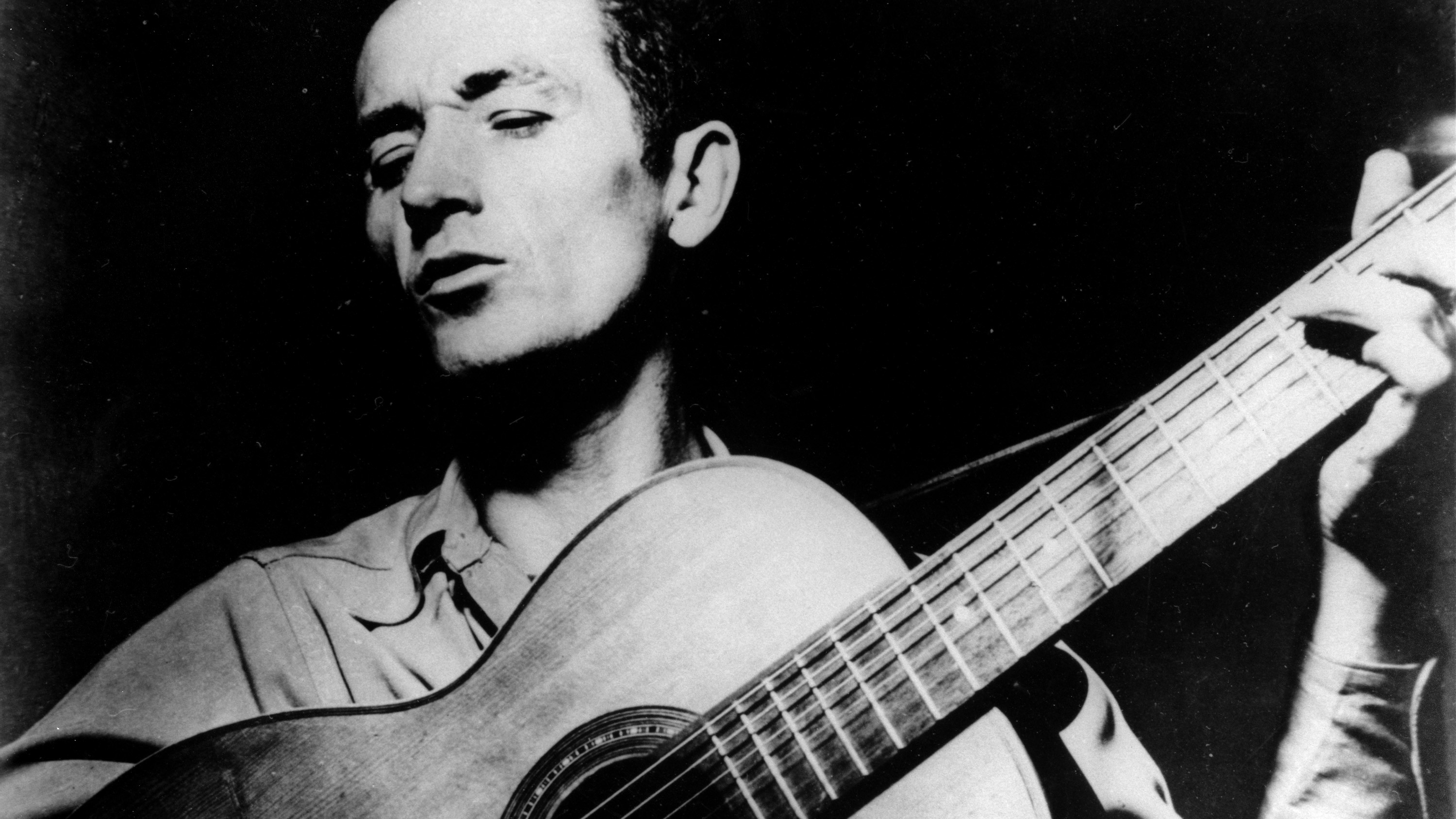 """This is an undated photograph of folk singer Woody Guthrie, singing a song and playing his guitar.  Guthrie has written hundreds of songs, celebrating migrant workers, pacifists, and underdogs.  Two of his well-known songs are """"So Long, It's Been Good to Know You,"""" and """"This Land is Your Land."""""""
