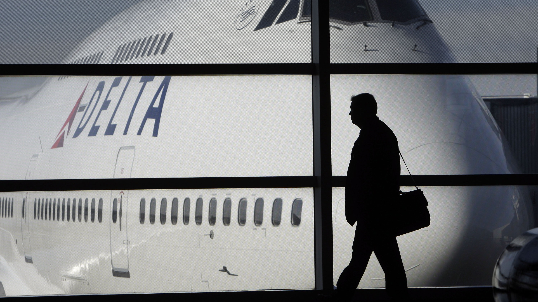 A passenger walks past a Delta Airlines 747 aircraft in McNamara Terminal at Detroit Metropolitan Wayne County Airport in Romulus, Mich.