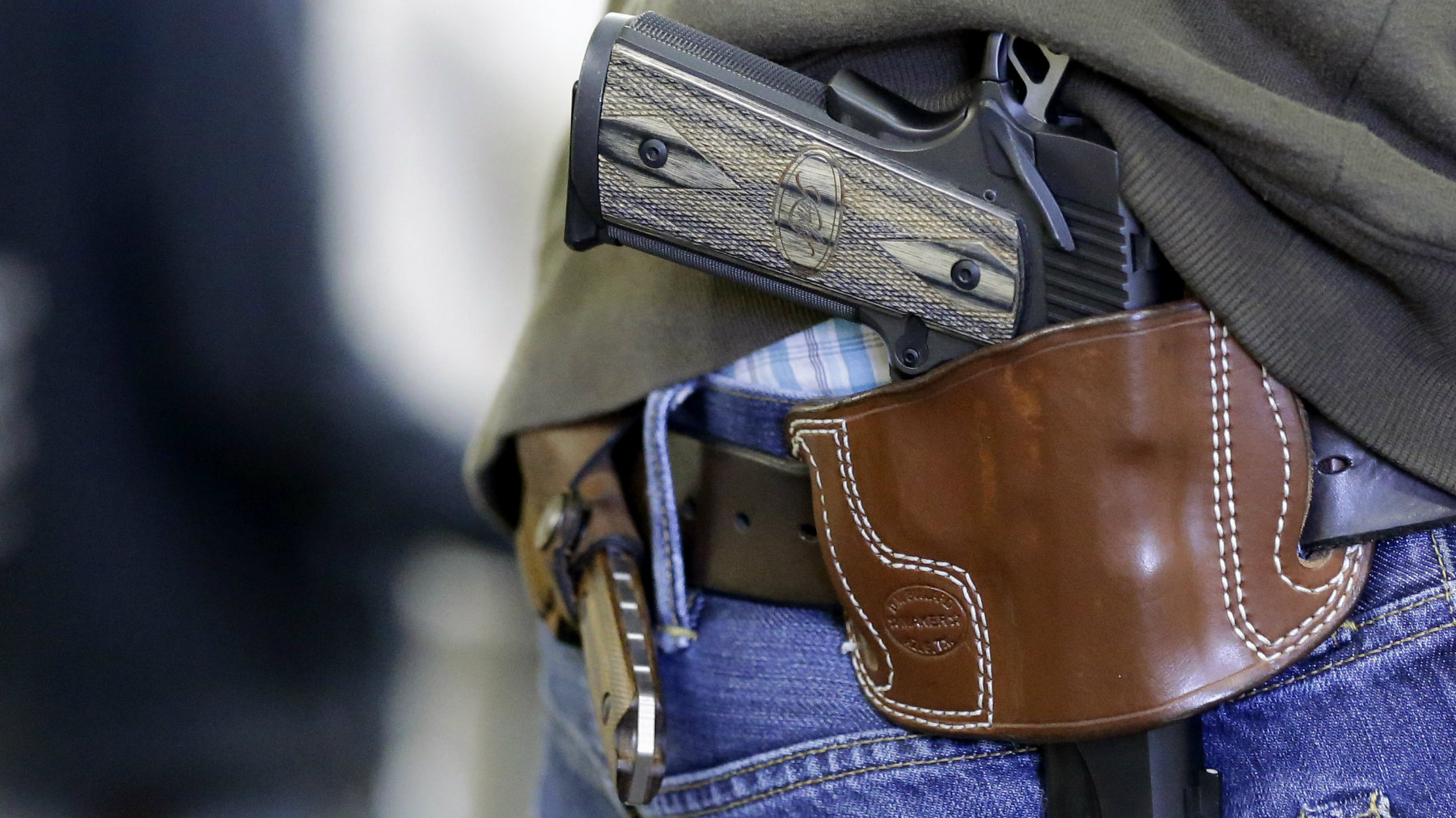 HOLD FOR MOVEMENT WITH STORY--Matt Nutt wears his gun on his hip as he works at the Spring Guns and Ammo store Monday, Jan. 4, 2016, in Spring, Texas. (AP Photo/David J. Phillip)