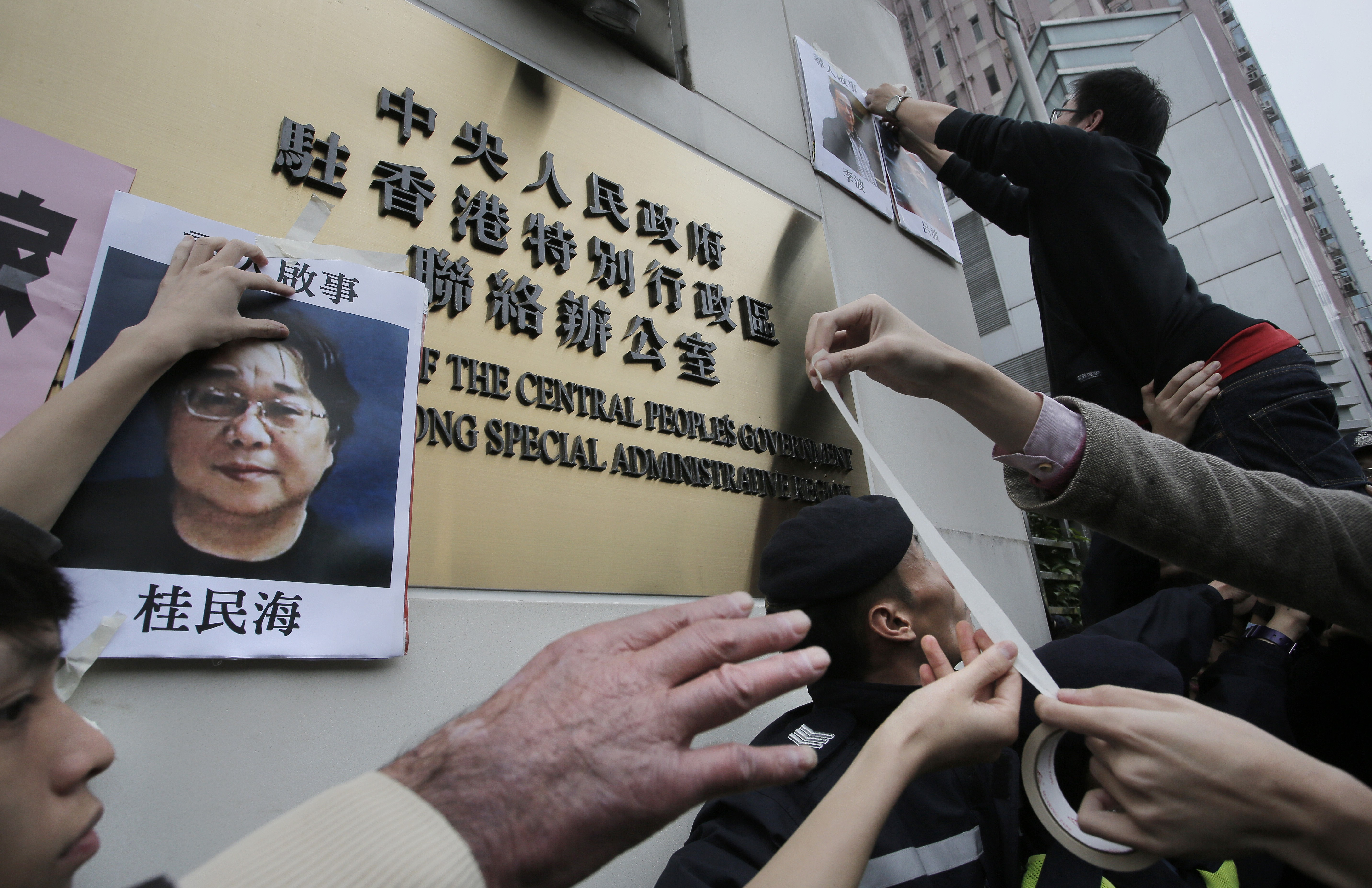 Protesters try to stick photos of missing booksellers during a protest outside the Liaison of the Central People's Government in Hong Kong, Sunday, Jan. 3, 2016. Hong Kong pro-democracy lawmakers say they'll press the government for answers after a fifth employee of a publisher specializing in books critical of China's ruling communists went missing. (AP Photo/Vincent Yu)