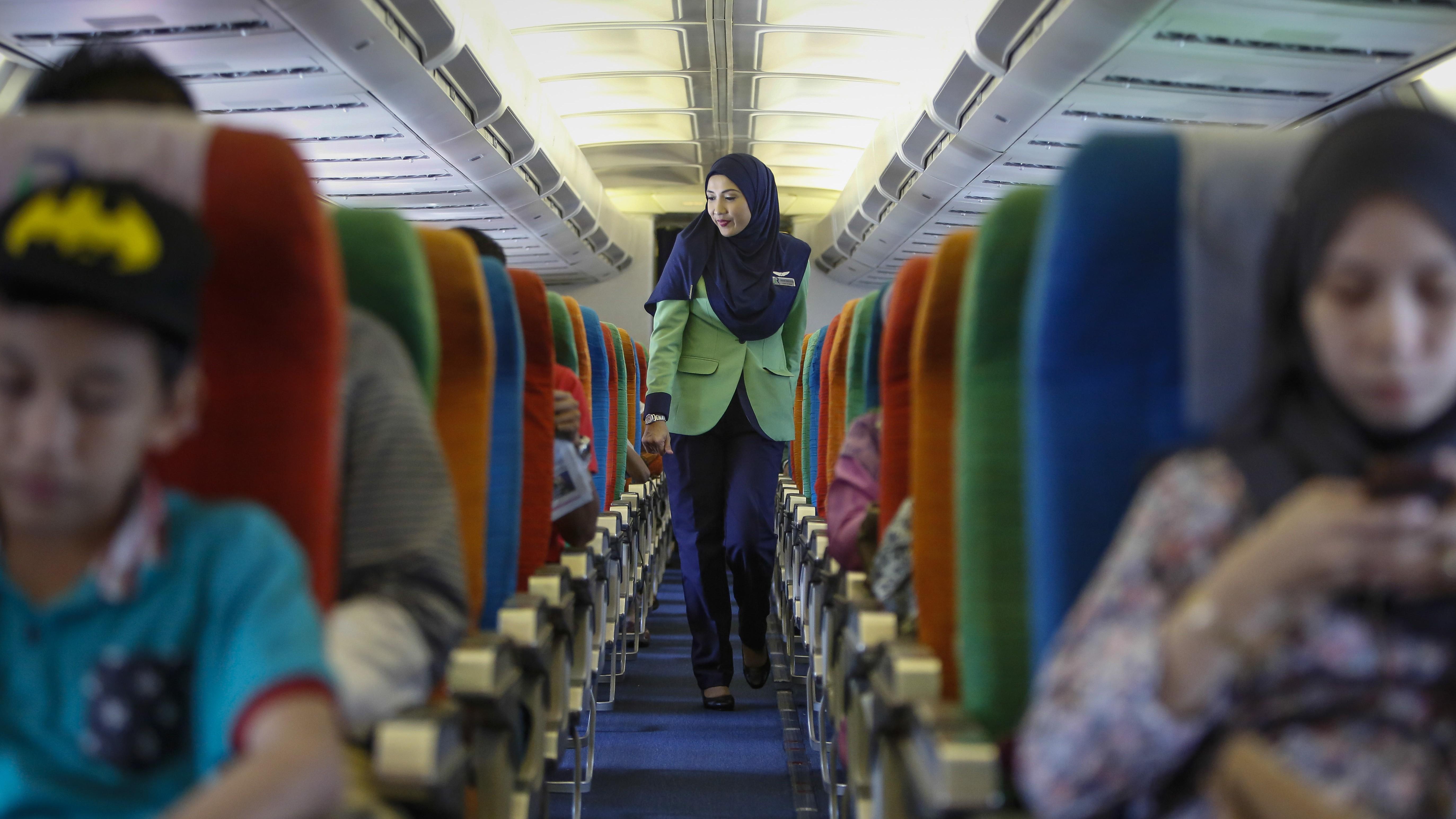 A Rayani Air flight attendant walks down the aisle on board before departure at Kuala Lumpur International Airport