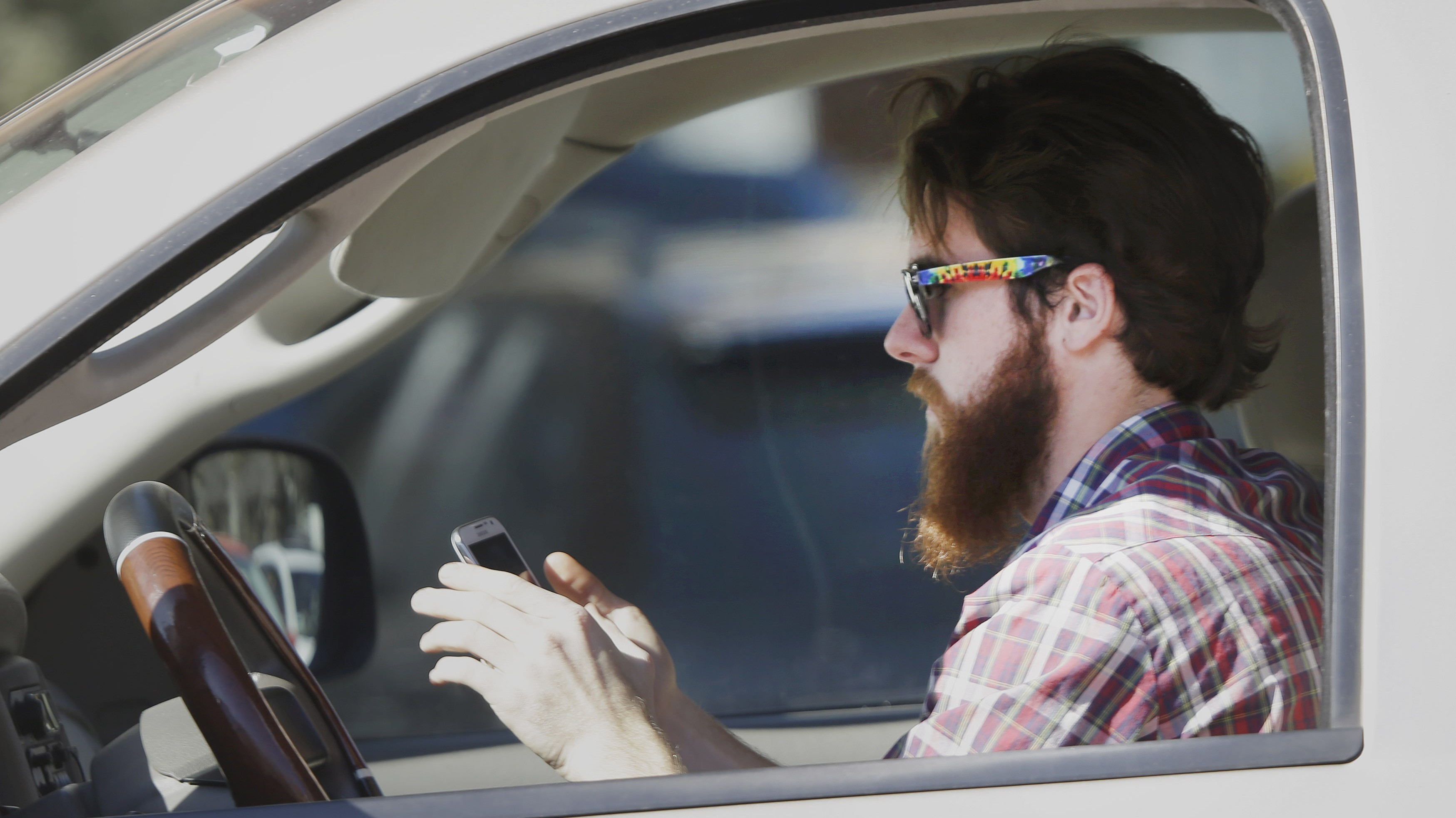 An man works his phone as he drives through traffic in Dallas, Tuesday, Feb. 26, 2013. Texas lawmakers are considering a statewide ban on texting while driving.