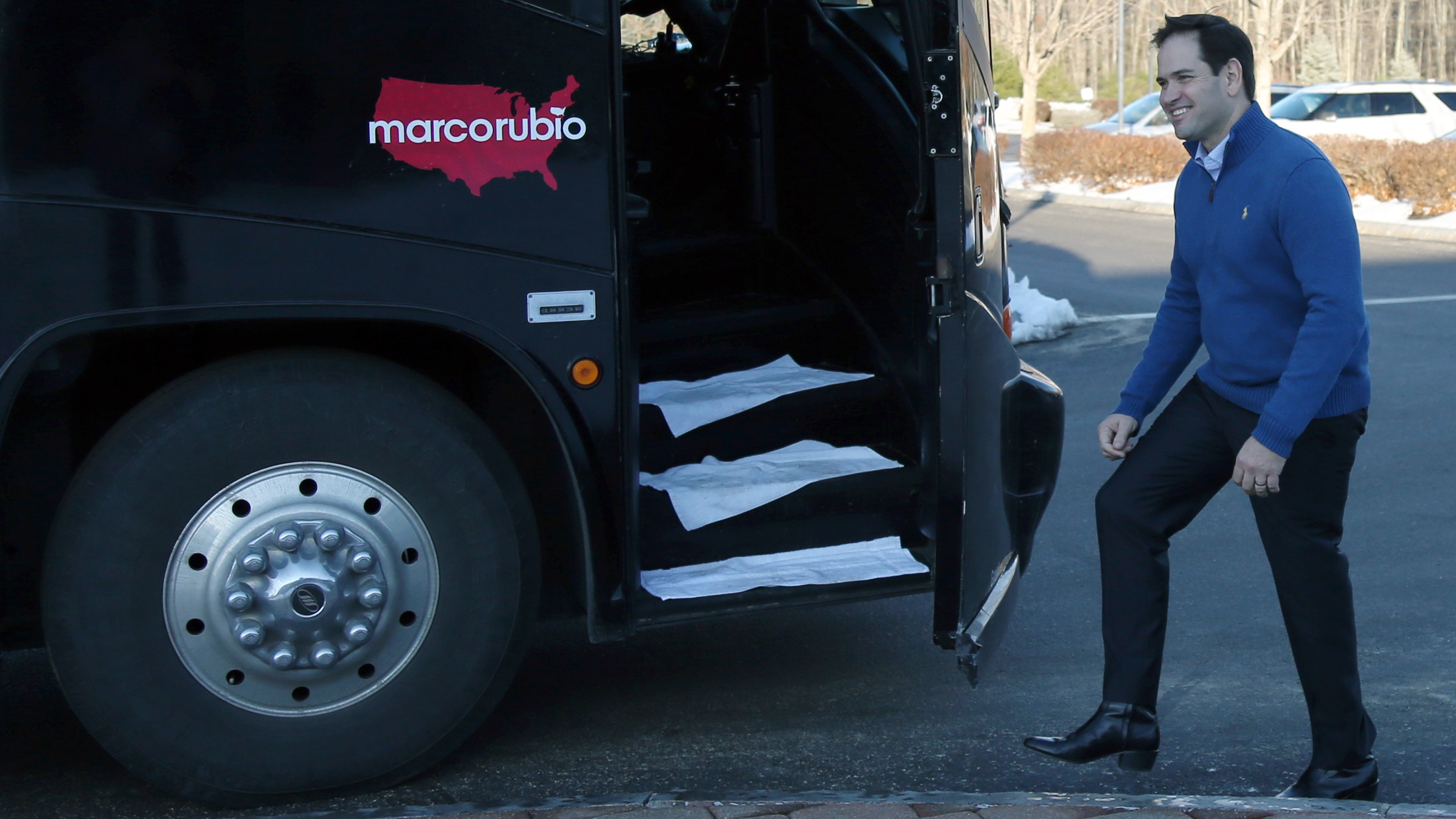 Republican presidential candidate Sen. Marco Rubio, R-Fla., smiles as he gets on his bus as he leaves a campaign stop, Sunday, Jan. 3, 2016, in Atkinson, N.H.