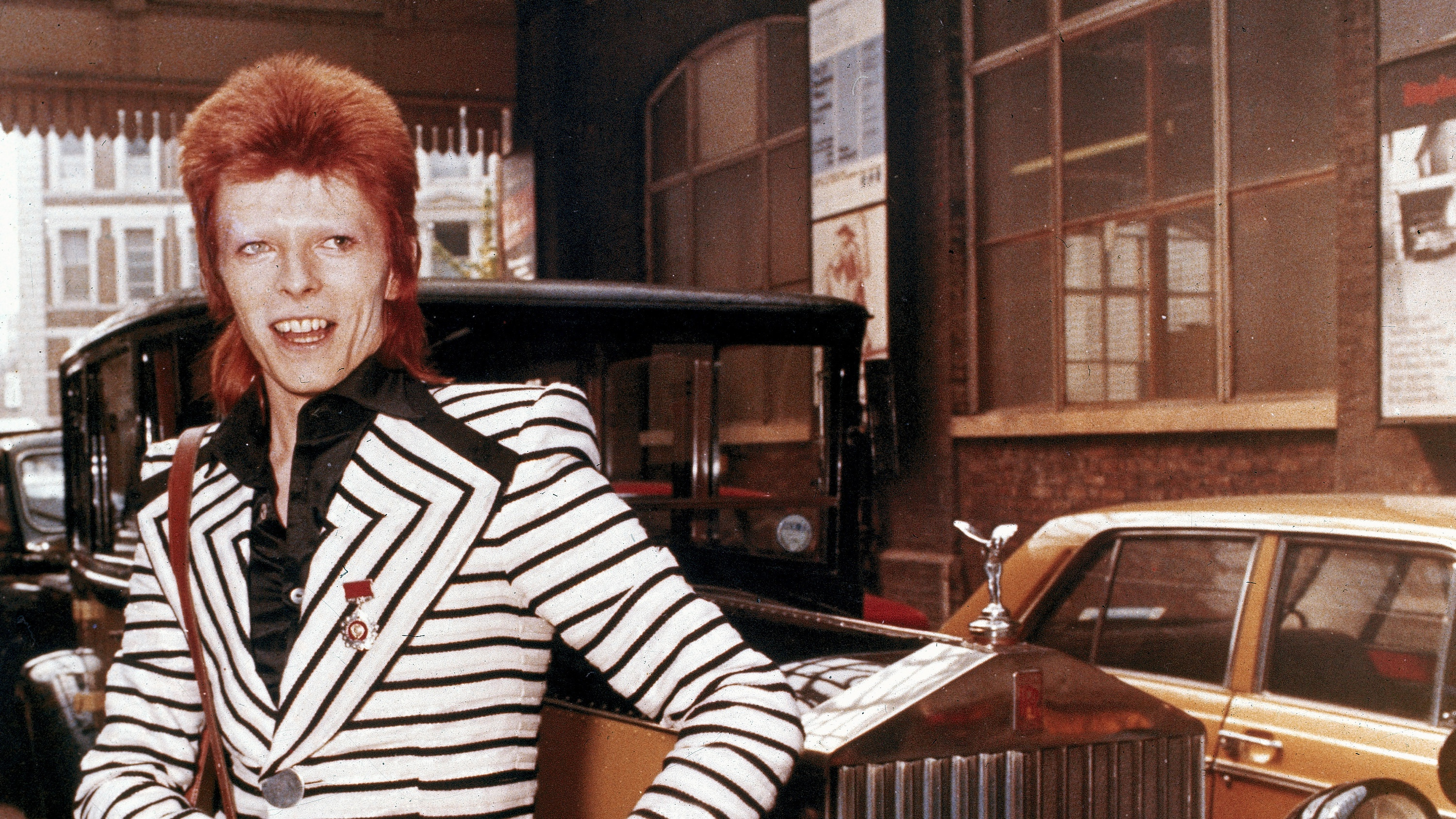 British rock singer, David Bowie, poses beside his Rolls Royce in May 1973.