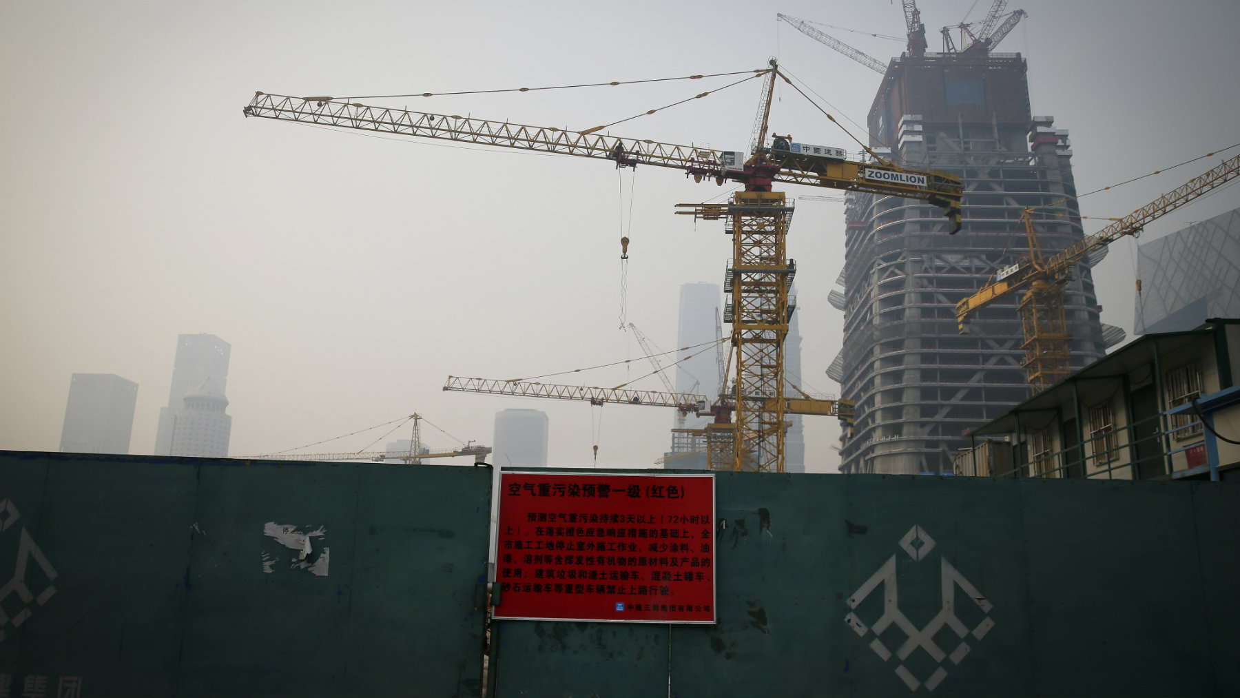 A red alert notice board is placed on the entrance gate of a construction site as the capital city shrouded with smog in Beijing.