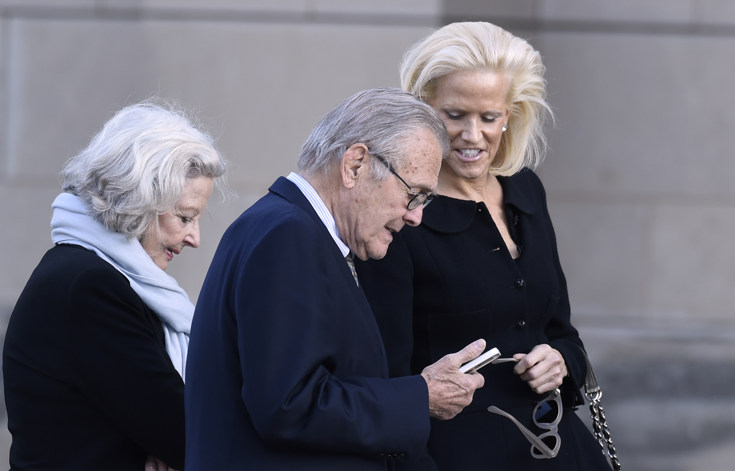 Former Defense Secretary Donald Rumsfeld and his wife Joyce, left, arrives for the funeral service for Ben Bradlee at the National Cathedral in Washington, Wednesday, Oct. 29, 2014. Bradlee led The Washington Post during some of its biggest years and proudest moments. (AP Photo/Susan Walsh)