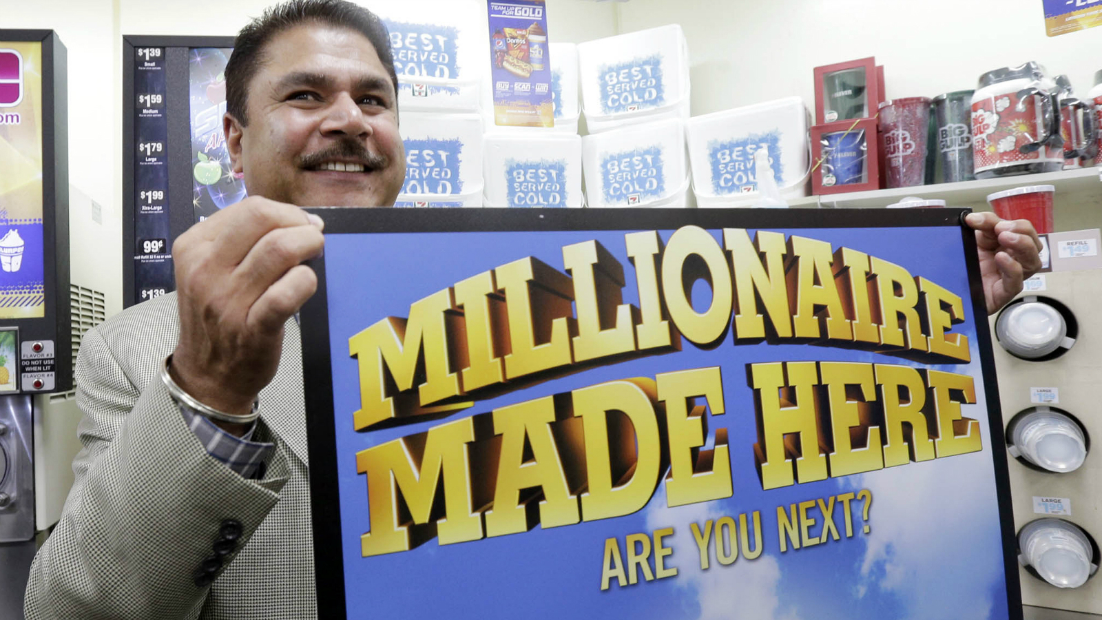 Balbir Atwal, the owner of a 7-Eleven store that sold a winning Powerball lottery ticket, holds up a Millionaire Made Here, sign at his store in Chino Hills, Calif., Thursday, Jan. 14, 2016. Atwal, says he was at home when a friend called to tell him that someone in Chino Hills had hit the jackpot. Atwal says he didn't know the ticket was purchased at his store until he turned on the TV.