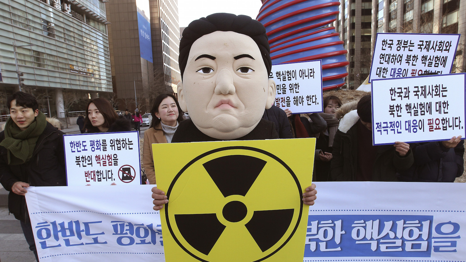 """A South Korean university student wearing a mask depicting North Korean leader Kim Jong Un participates in a rally against North Korea's announcement that it had tested a hydrogen bomb in Seoul, South Korea, Thursday, Jan. 7, 2016. North Korea's declaration that it had tested a hydrogen bomb for the first time was greeted with widespread condemnation - but also skepticism  - as world powers vowed Wednesday to punish the impoverished and defiant nation with new international sanctions. The banners read """" We denounce North Korea' nuclear test."""" ()"""