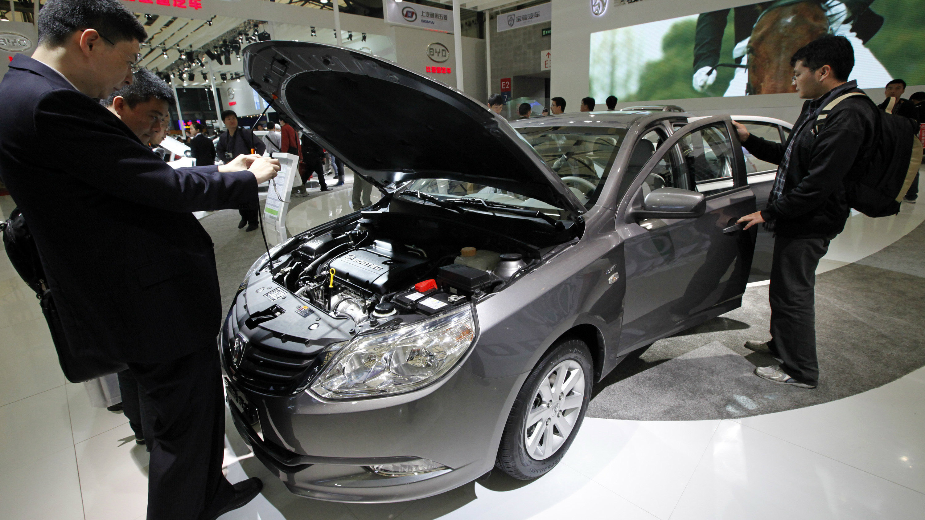 In this photo taken Thursday, April 21, 2011, visitors look at a new Baojun 630 sedan at the Shanghai International Auto Show in Shanghai, China. General Motors unveiled the first model of its new car brand Baojun aimed specifically market at China. (AP Photo/Eugene Hoshiko)