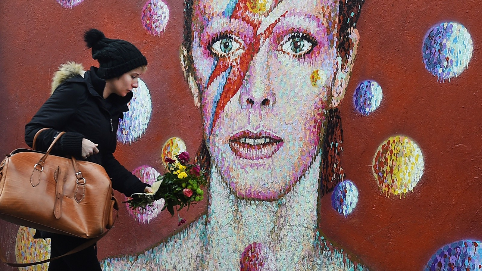 epa05096790 A women lays flowers at a mural of British singer David Bowie in Brixton, birth place of the late David Bowie in London, Britain, 11 January 2016. Well-wishers have flocked to the Bowie mural to pay their respects following the announcement of his death. According to reports quoting David Bowie's son and his official Facebook page, Bowie, 69, has died on 10 January 2016 after a battle with cancer.  EPA/ANDY RAIN