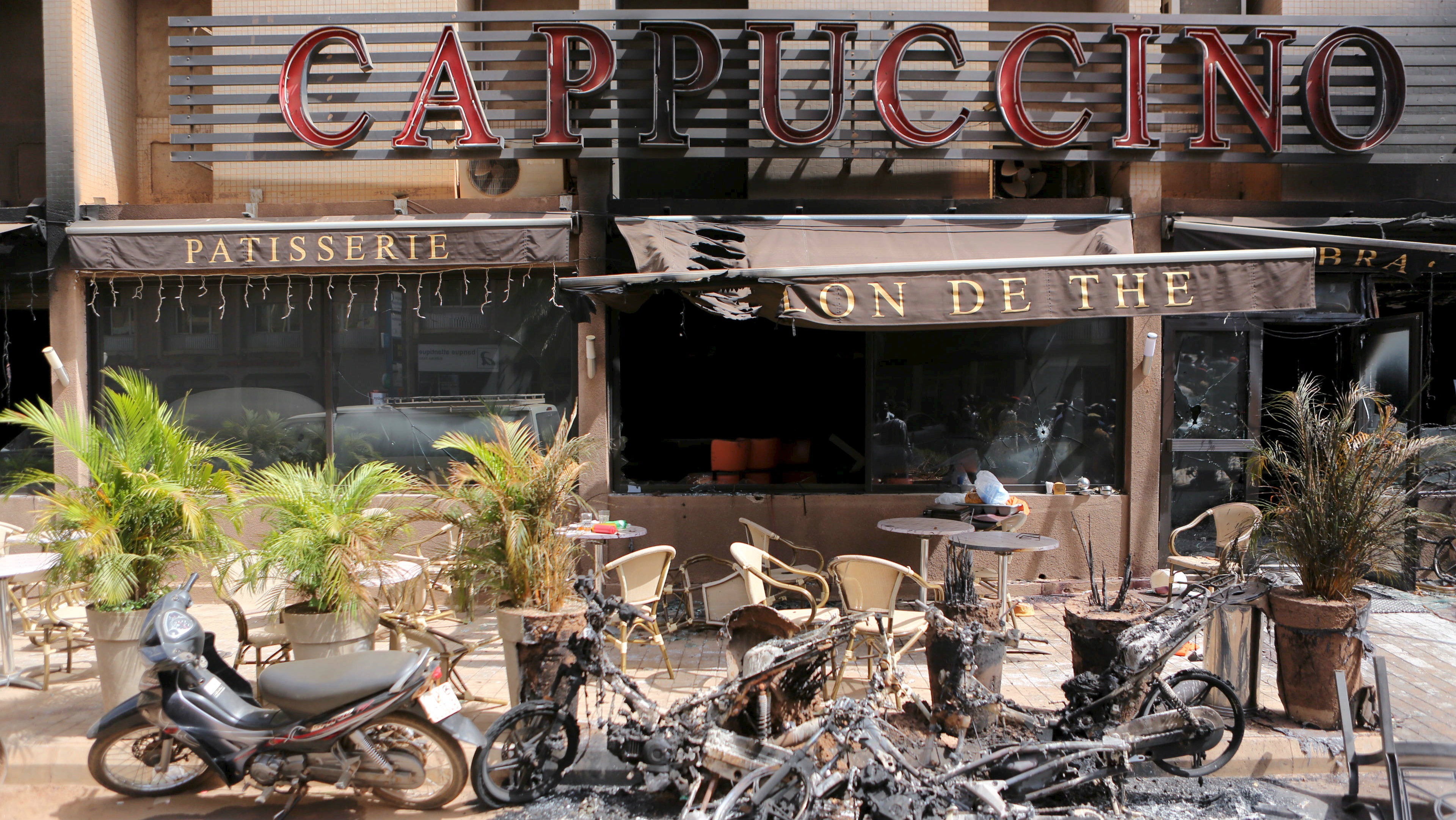 """The burned-out exterior of """"Cappuccino"""" restaurant is seen in Ouagadougou, Burkina Faso, January 17, 2016, a day after security forces retook the Splendid Hotel from al Qaeda fighters who seized it in an assault that killed two dozen people from at least 18 countries and marked a major escalation of Islamist militancy in West Africa."""