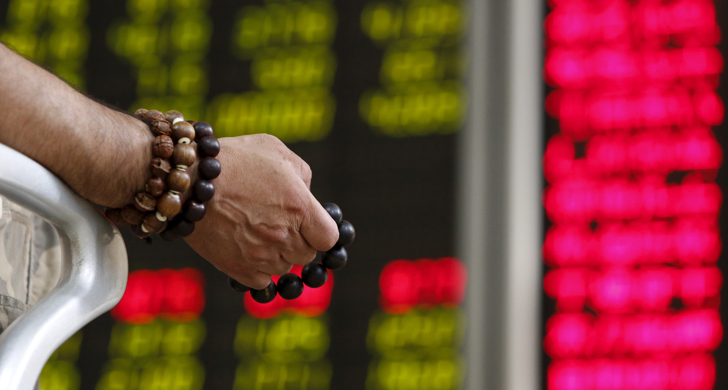 An investor holds onto prayer beads as he watches a board showing stock prices at a brokerage office in Beijing