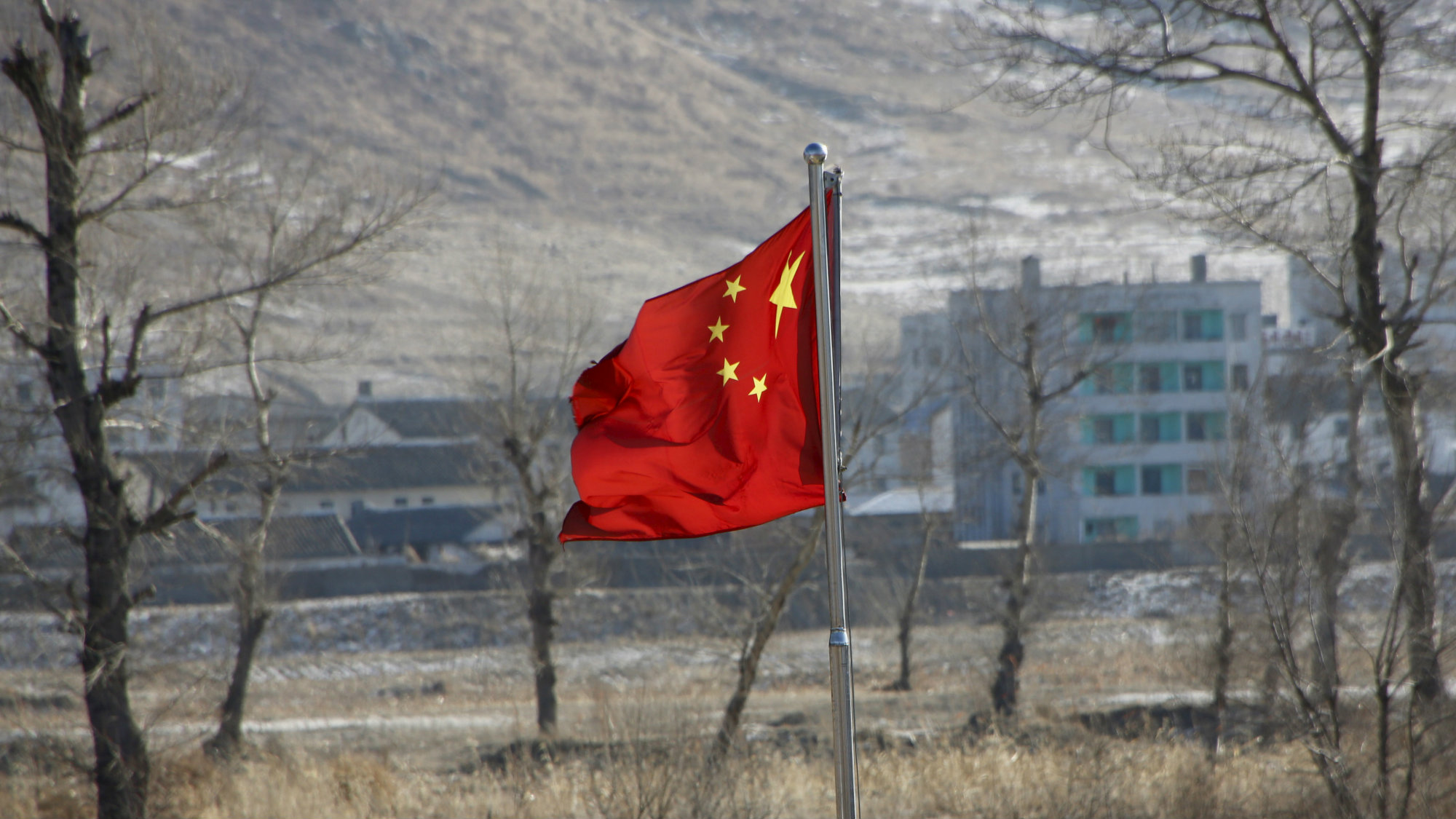 DATE IMPORTED:January 07, 2016China's national flag flutters on the Chinese side of the banks of the Tumen river, as a North Korean village is seen behind, in Tumen, China, January 7, 2016. REUTERS/Kim Kyung-Hoon