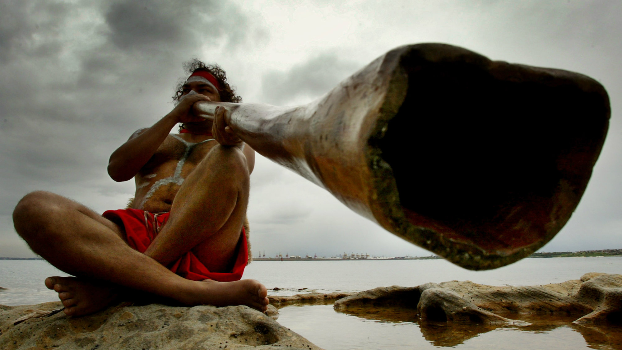 Aboriginal peformer Les Saxby plays a traditional aboriginal musical instrument known as a didgeridoo on the shores of Sydney's Botany Bay April 29, 2002 during the Meeting of Two Cultures ceremony.