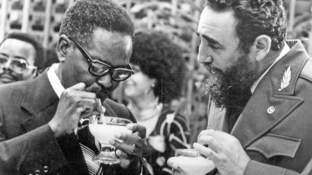 Cuban Prime Minister Fidel Castro, right, shows Angolan Movimento Popular de Liberta��o de Angola (MPLA) President Agostinho Neto how to drink a daikiri, a frozen Cuban drink made with rum, ice and sugar, during a reception in his honor in Havana, July 28, 1976.
