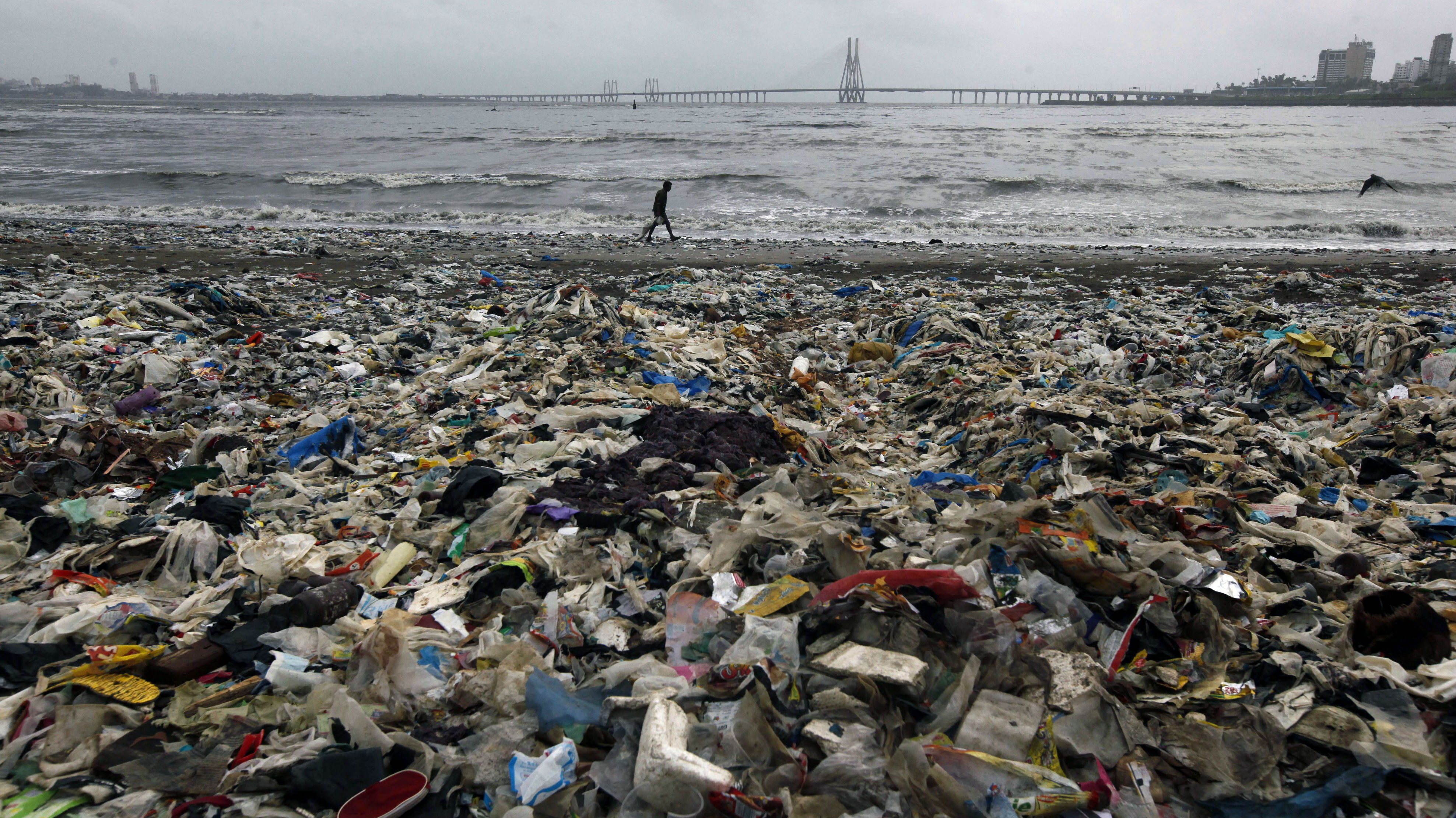A man walks by the Arabian Sea coast piled with garbage, mostly plastic waste, in Mumbai, India, Monday, July 30, 2012.
