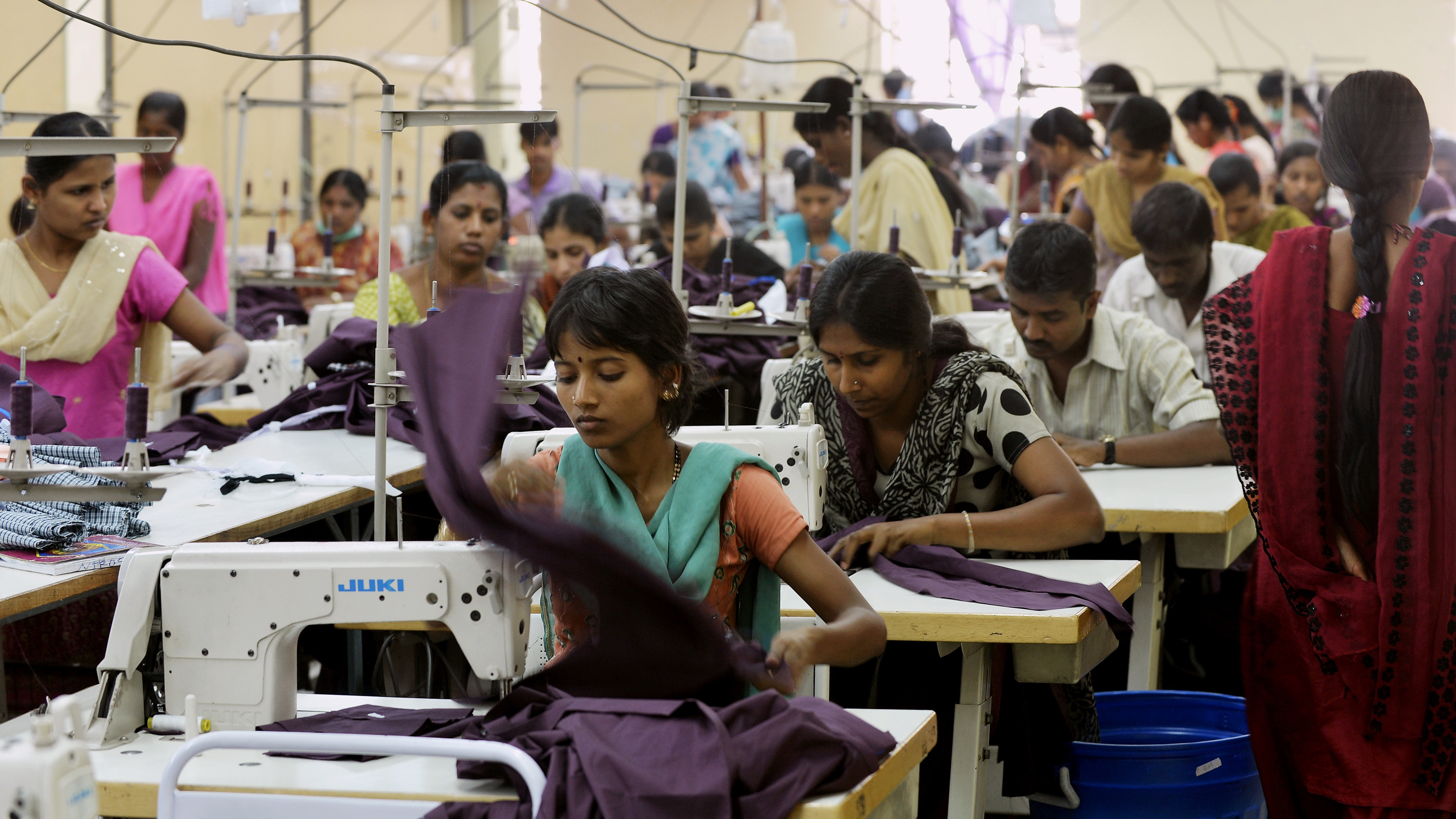 Indian workers of a private garment factory use machines while stitching apparel in Bangalore on November 21, 2012.