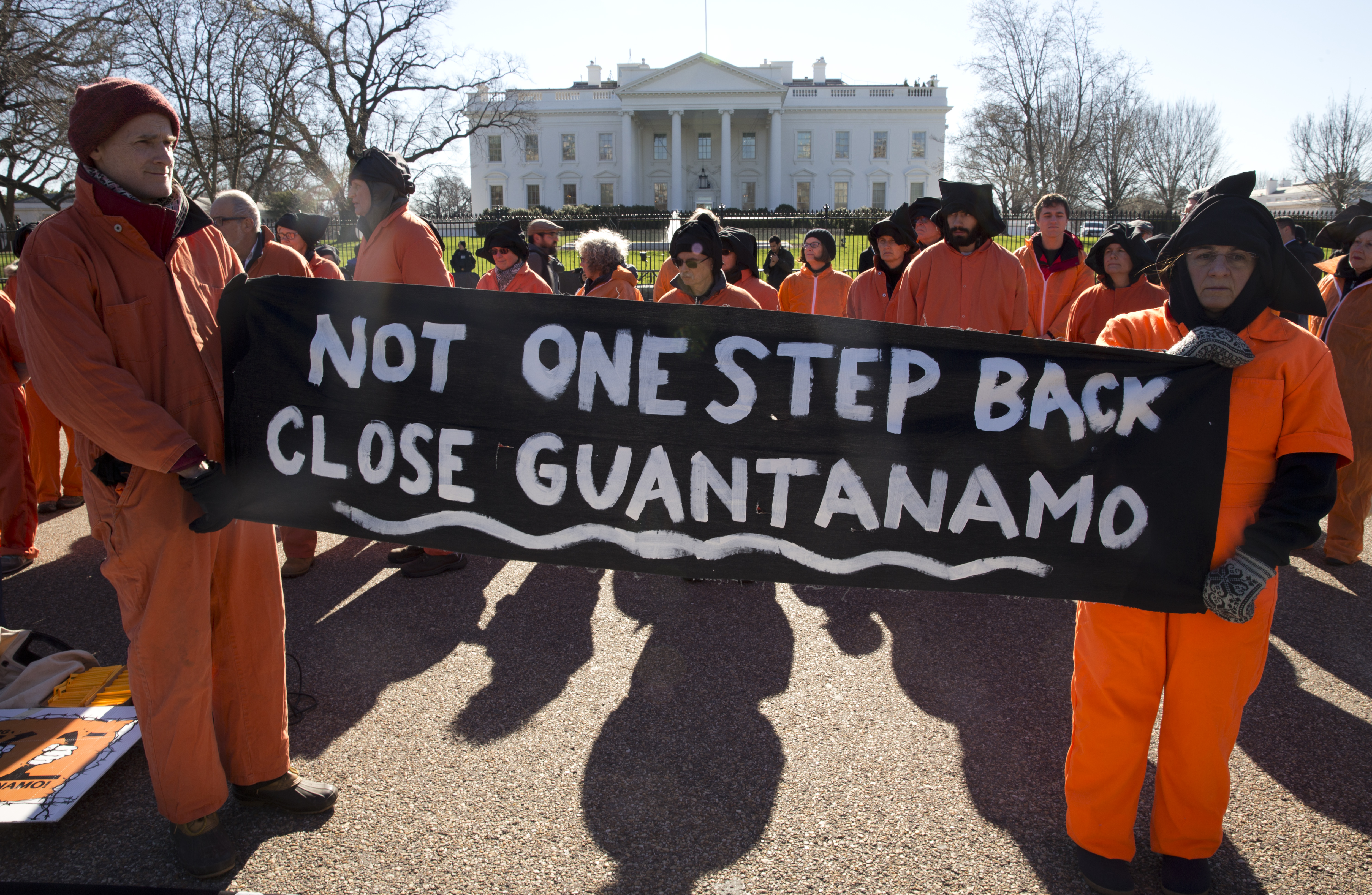 "Protesters wearing orange jumpsuits depicting Guantanamo Bay detainees, hold a sign that reads ""Not One Step Back Close Guantanamo"" participate in a rally outside of the White House in Washington Monday, Jan. 11, 2016, calling for a close of the detention center at the U.S. base at Guantanamo Bay, Cuba."