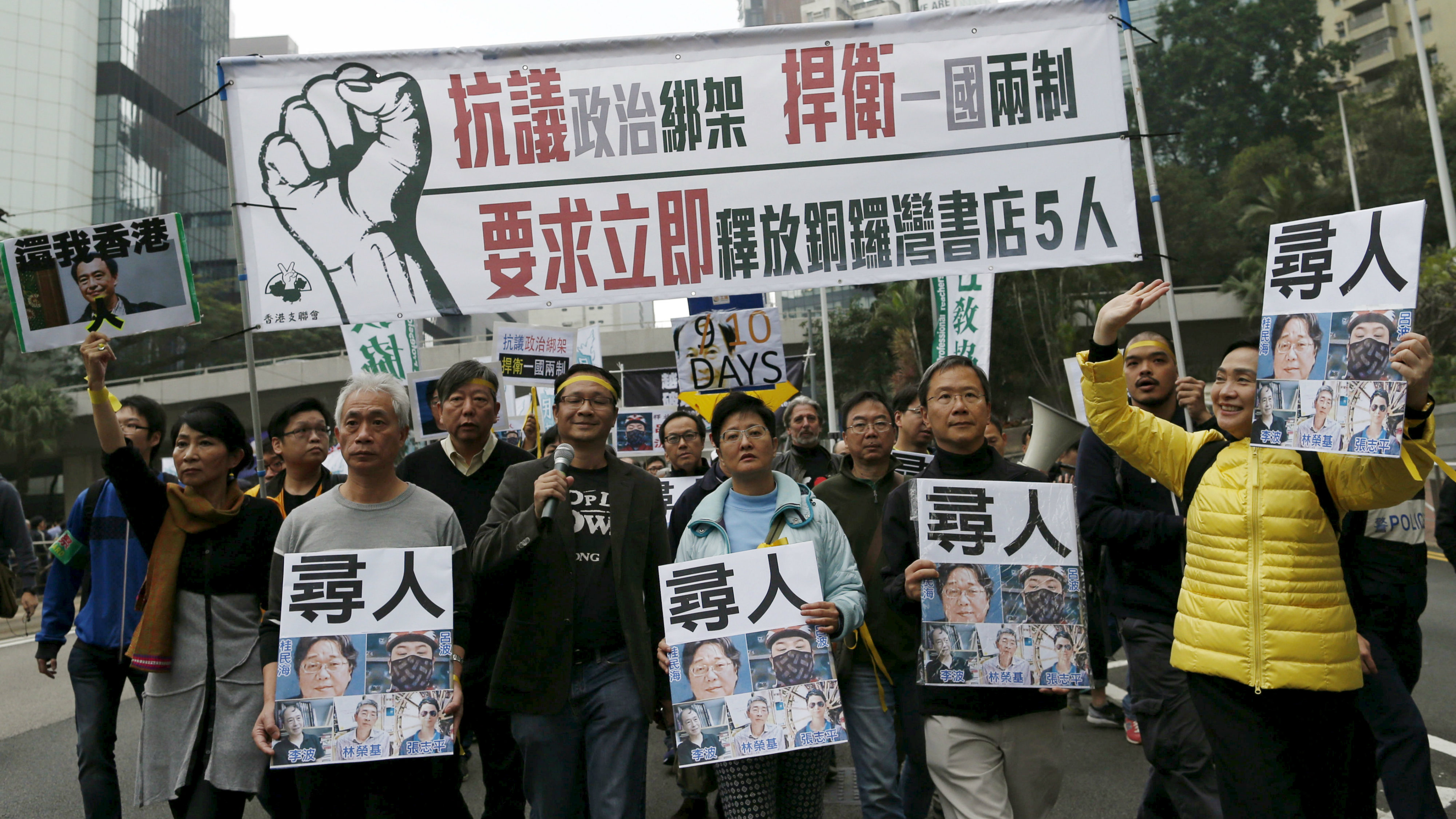Demonstrators hold up portraits of five missing booksellers in Hong Kong.