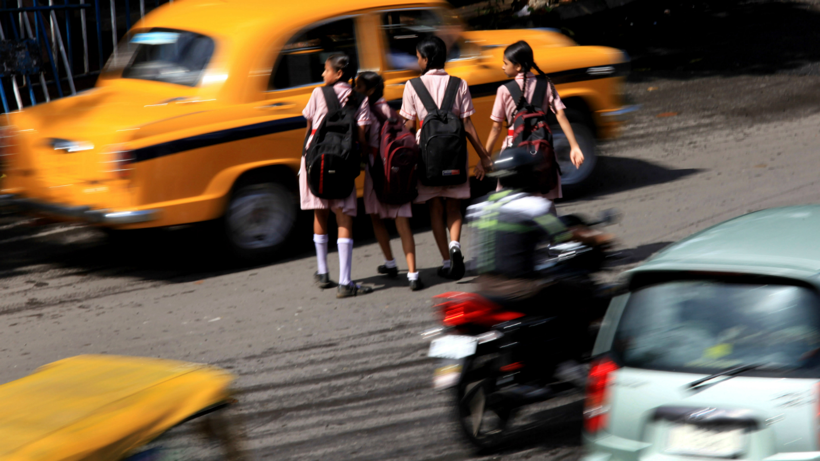 Indian students try to cross in the middle of a busy road in Calcutta, Eastern India, 17 July 2013. According to reports, there are 125,000 fatalities brought about by road accidents annually. Media reports on 17 July announced government plans to prohibit vehicles carrying loads that protrude up to one meter outside a vehicle's frame in order to limit accidents.