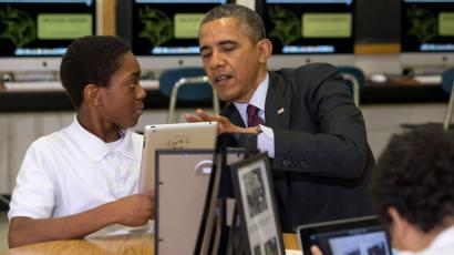 President Barack Obama looks at a student's iPad project at Buck Lodge Middle School in Adelphi, Md., Tuesday, Feb. 4, 2014, where he spoke about his ConnetED goal of connecting 99% of students to next generation broadband and wireless technology within five years. (AP Photo/Jacquelyn Martin