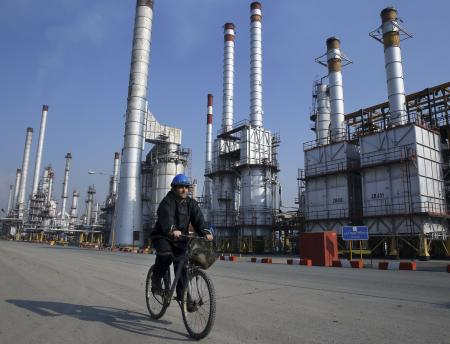 An Iranian oil worker rides his bicycle at the Tehran oil refinery, south of the capital Tehran, Iran. Across a Mideast fueled by oil production, low global prices have some countries running on empty and scrambling to cover shortfalls, even as more regional crude is on tap to enter the market.