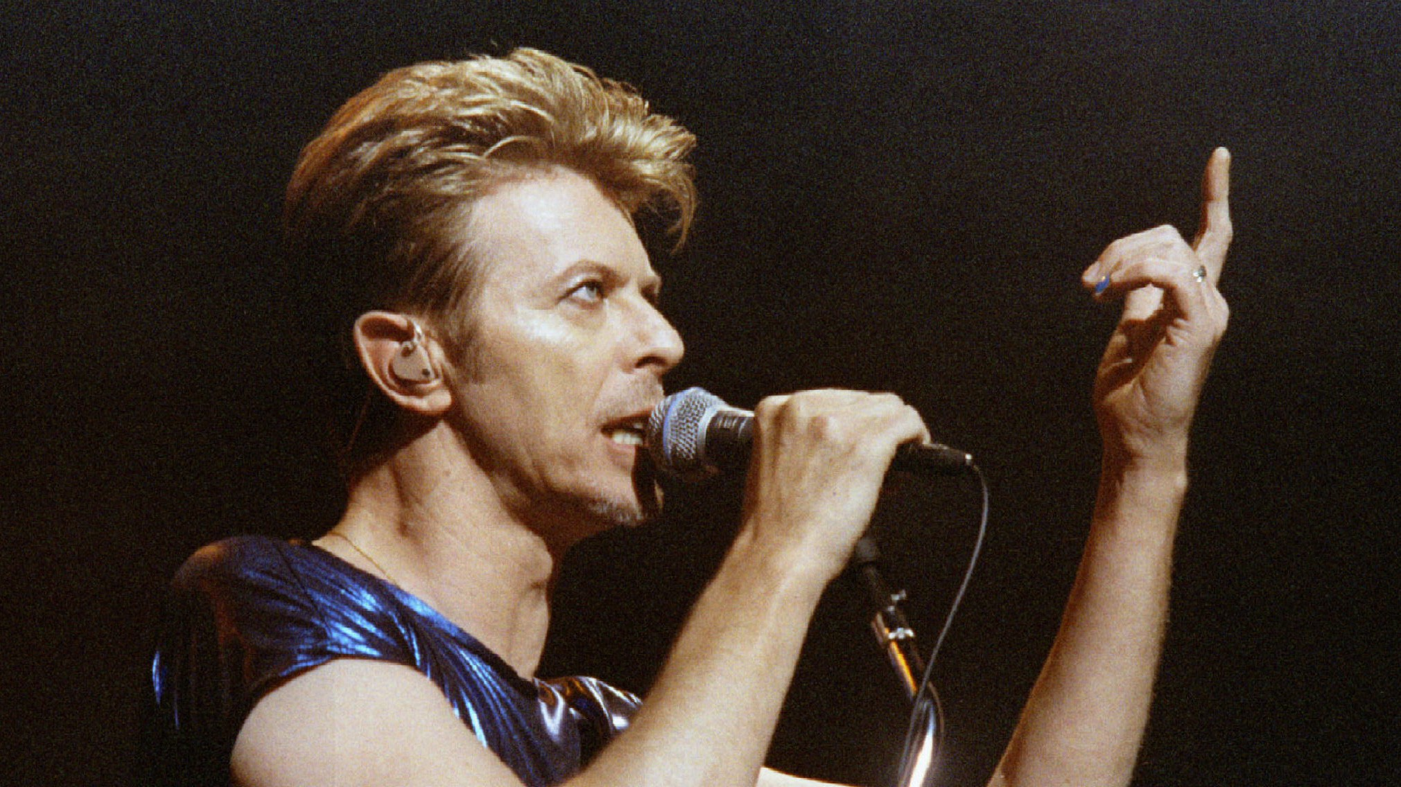 David Bowie gesturing on stage, lifting a finger.