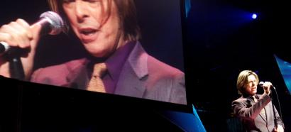 Bowie on stage against a large video screen showing his visage in 2000
