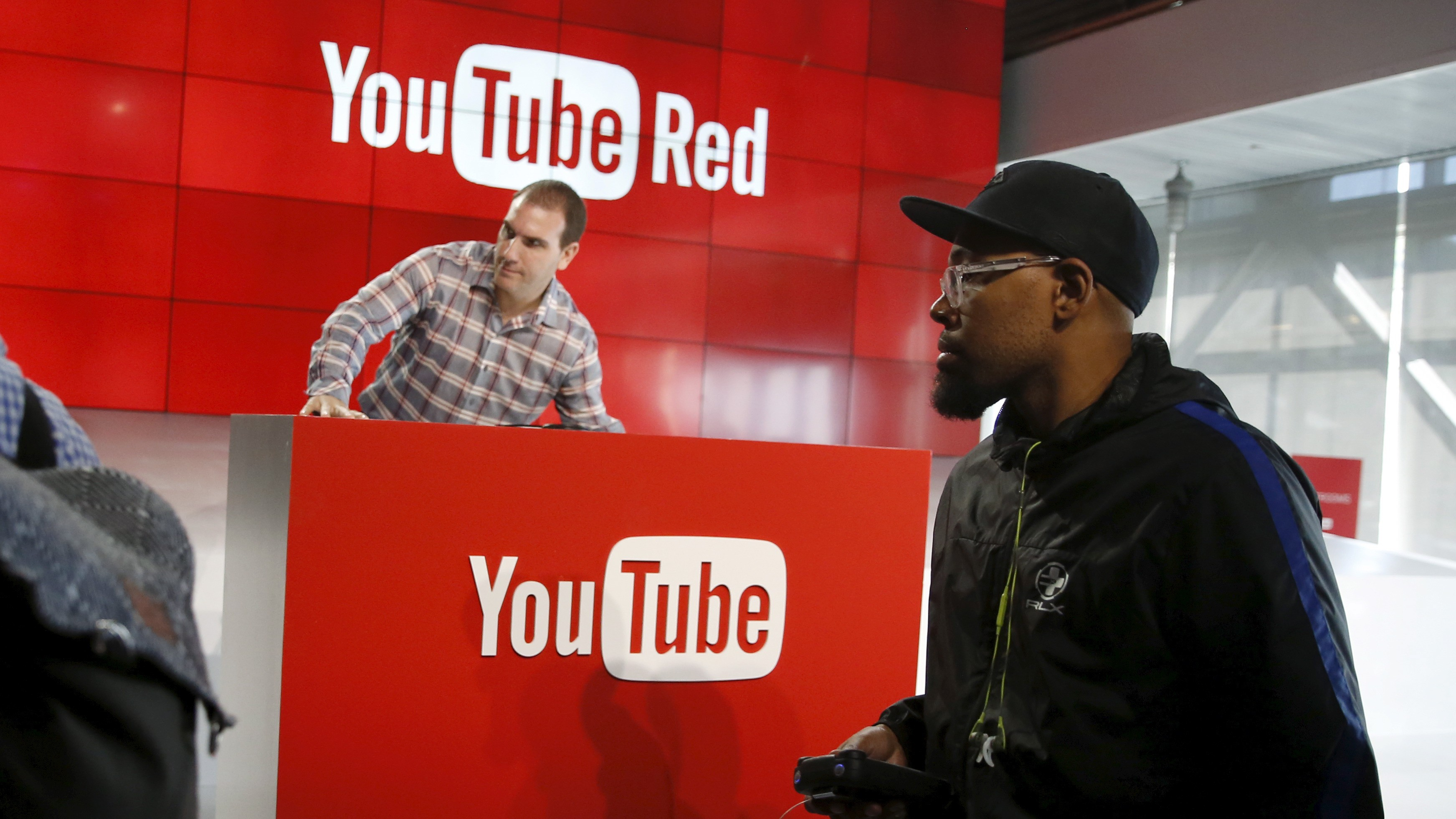 A man with camera walks past a YouTube Red podium