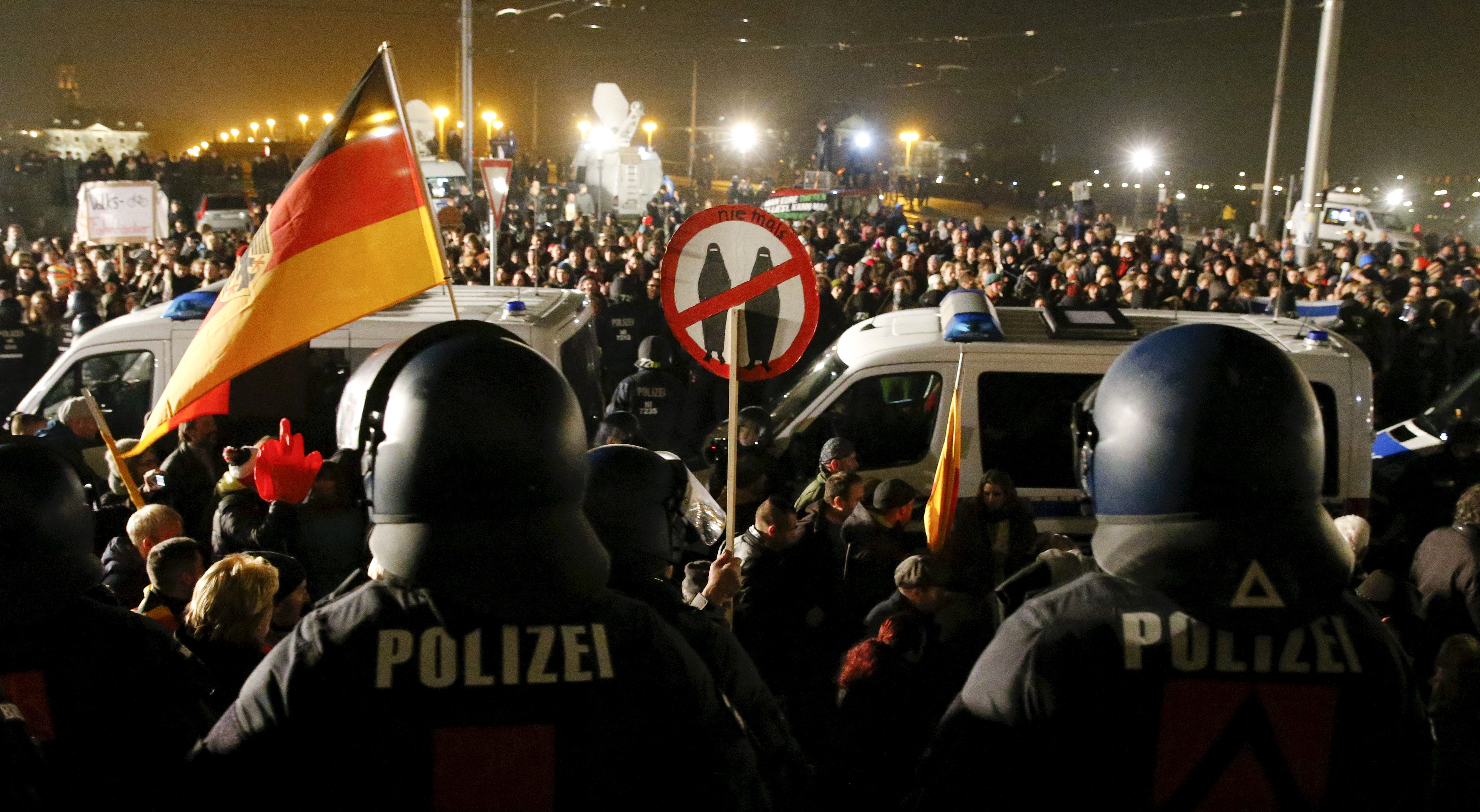 Police form a barrier observing People attending an anti-immigration demonstration in Dresden