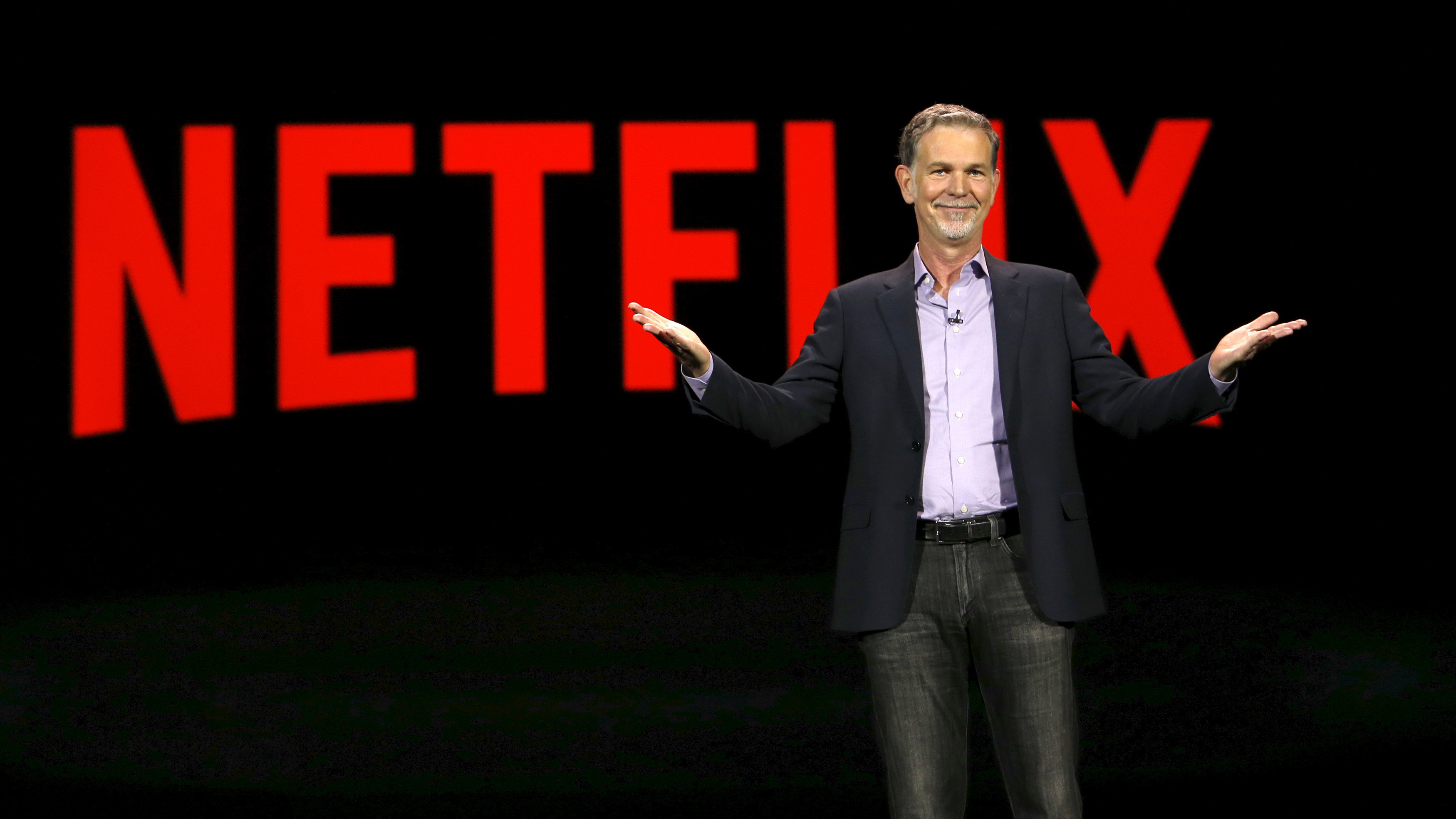 Reed Hastings shrugs on stage with Netflix logo behind