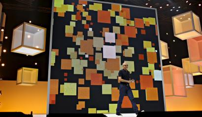 Microsoft CEO Satya Nadella strides on stage with a backdrop of orange blocks