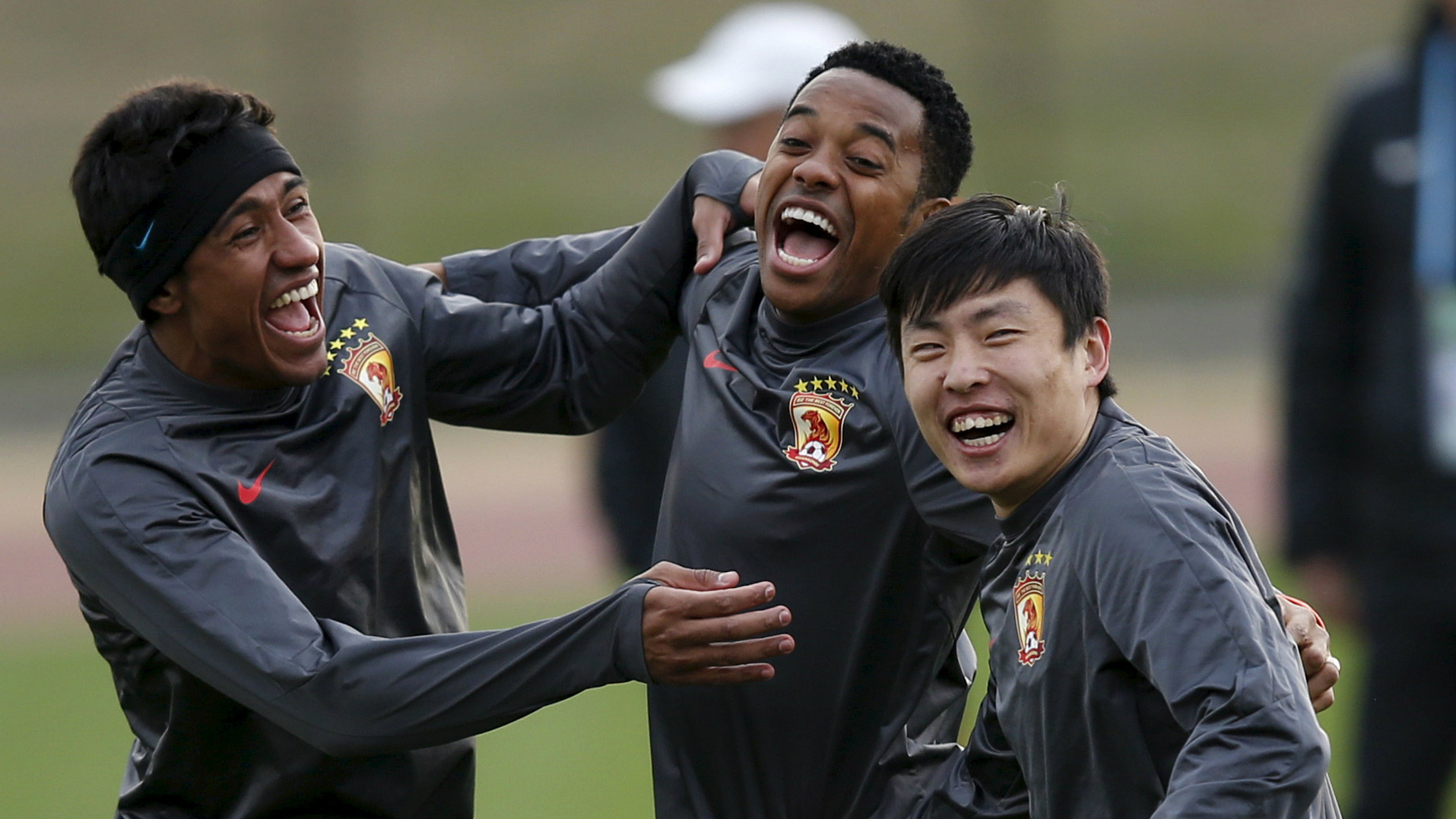 Guangzhou Evergrande's Paulinho, Robinho and Zheng Long (L-R) laugh during a training session ahead of their Club World Cup semi-final soccer match against Barcelona in Yokohama, south of Tokyo, Japan, December 15, 2015.