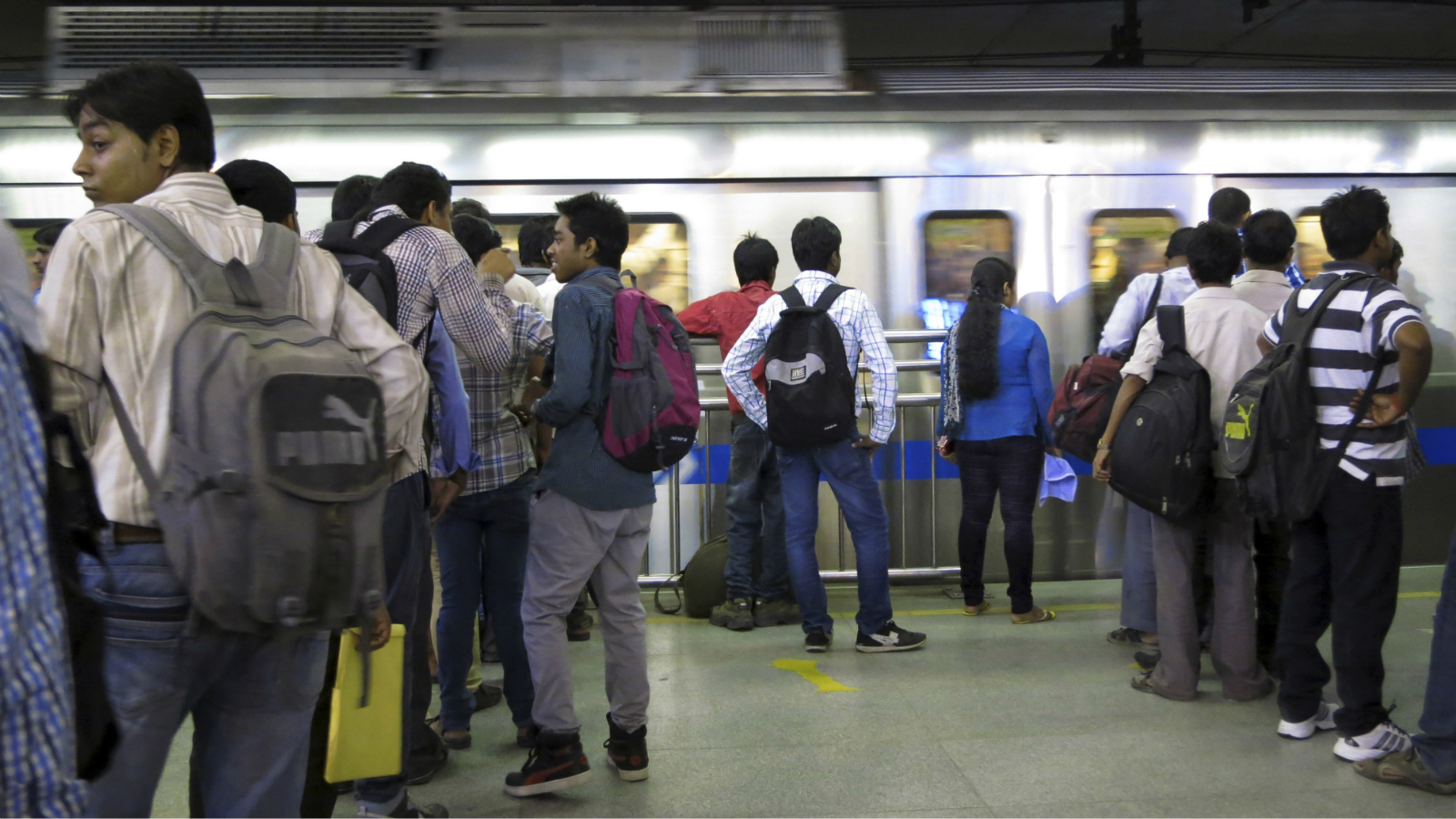 An metro train pulls into a station as an Indian woman waits to board it, surrounded by men in New Delhi, a city fast acquiring an image of being unsafe for women, India, Friday, Sept. 13, 2013. An Indian judge is expected to hand down sentences Friday in the fatal gang rape of a young woman on a New Delhi bus, with the prosecutor and others calling for the four convicted rapists to be executed. The men were convicted Tuesday in the December attack of the 23-year-old woman, a brutal crime that unleashed a wave of public anger over the treatment of women in India. (AP Photo/Yirmiyan Arthur)