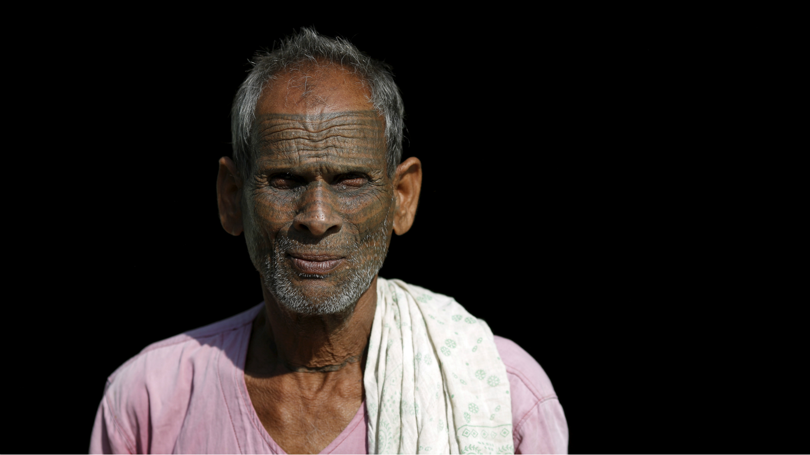 Bishram, 70, a follower of Ramnami Samaj, who has tattooed the name of the Hindu god Ram on his face, poses for a picture outside his house in the village of Arjuni, in the eastern state of Chhattisgarh, India, November 15, 2015. REUTERS/Adnan Abidi