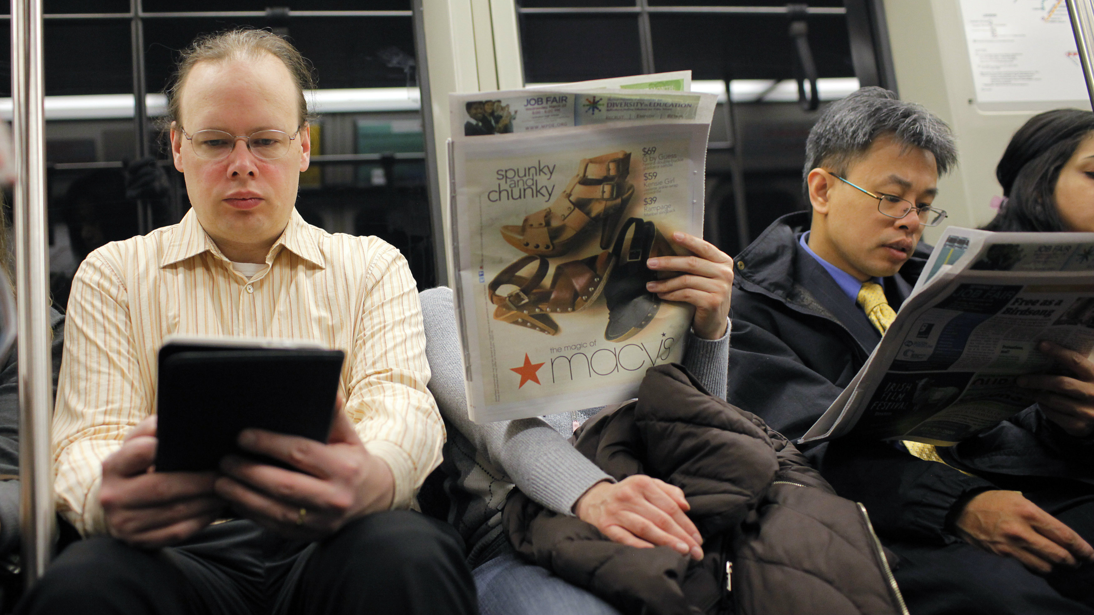 A commuter (L) reads on a Kindle e-reader while riding the subway in Cambridge, Massachusetts March 18, 2011. Publishers are adapting to rising sales of e-books, and the popularity of smart phones and tablets such as the iPad. The retail landscape has changed with Amazon becoming the dominant seller of books while countless book stores go the way of video rental stores. America's No. 2 book store chain, Borders, is bankrupt. Some authors have dropped their publishers entirely, self-publishing online and using social media to connect with readers. Picture taken March 18, 2011. To match Special Report PUBLISHING/EBOOKS/ REUTERS/Brian Snyder (UNITED STATES - Tags: MEDIA BUSINESS SCI TECH)