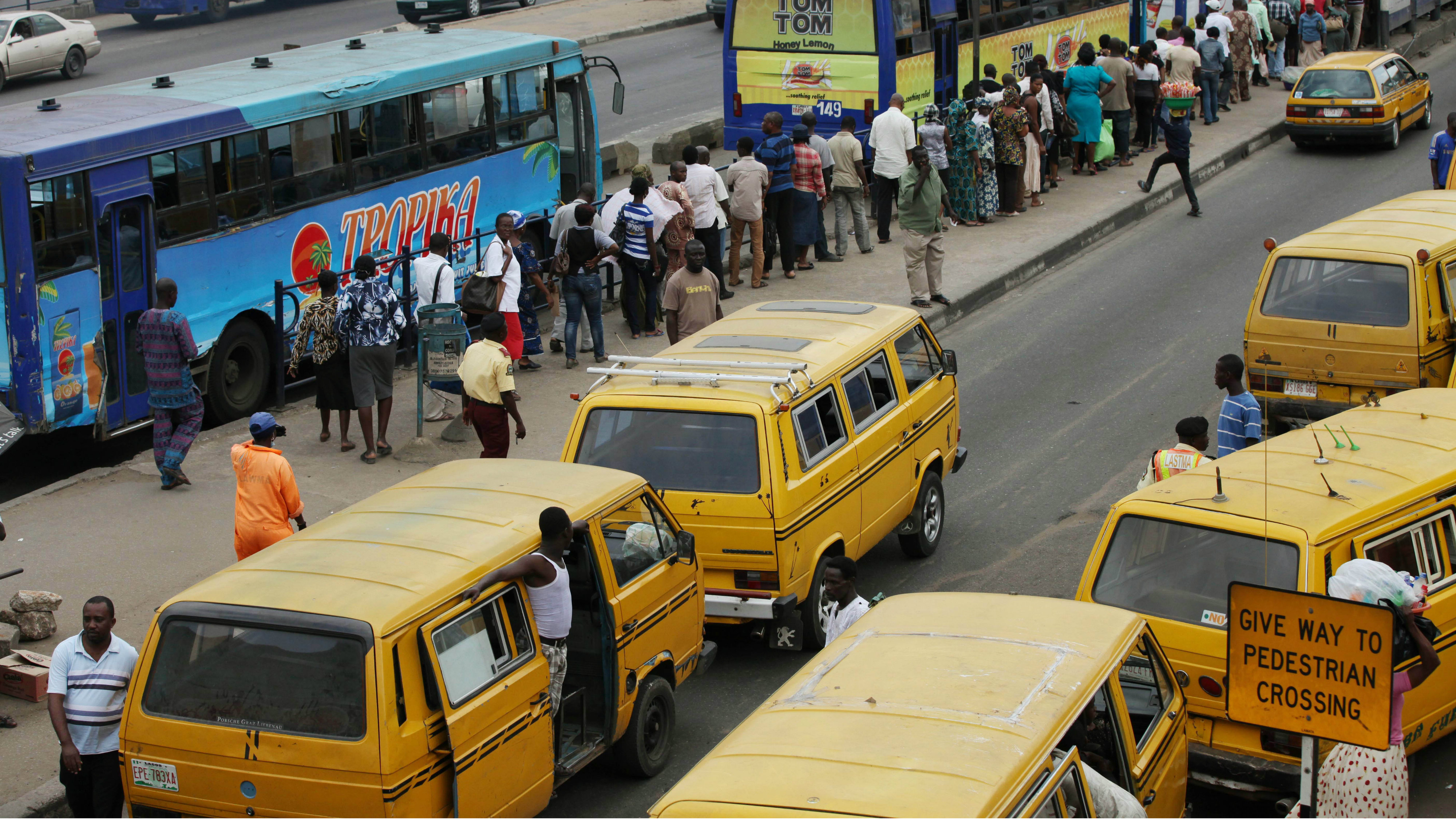 ADVANCE FOR USE MONDAY, OCT. 1, 2012 AND THEREAFTER - In this Wednesday, Aug. 15, 2012 photo, a long line of people waits to board a bus in Lagos, Nigeria. (AP Photo/Sunday Alamba)